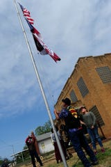 LilliyAna Hernandez, 12, shades her eyes as she watches as her flag is raised over Ranger City Hall Saturday. The sixth-grader's design was chosen from 101 entries.