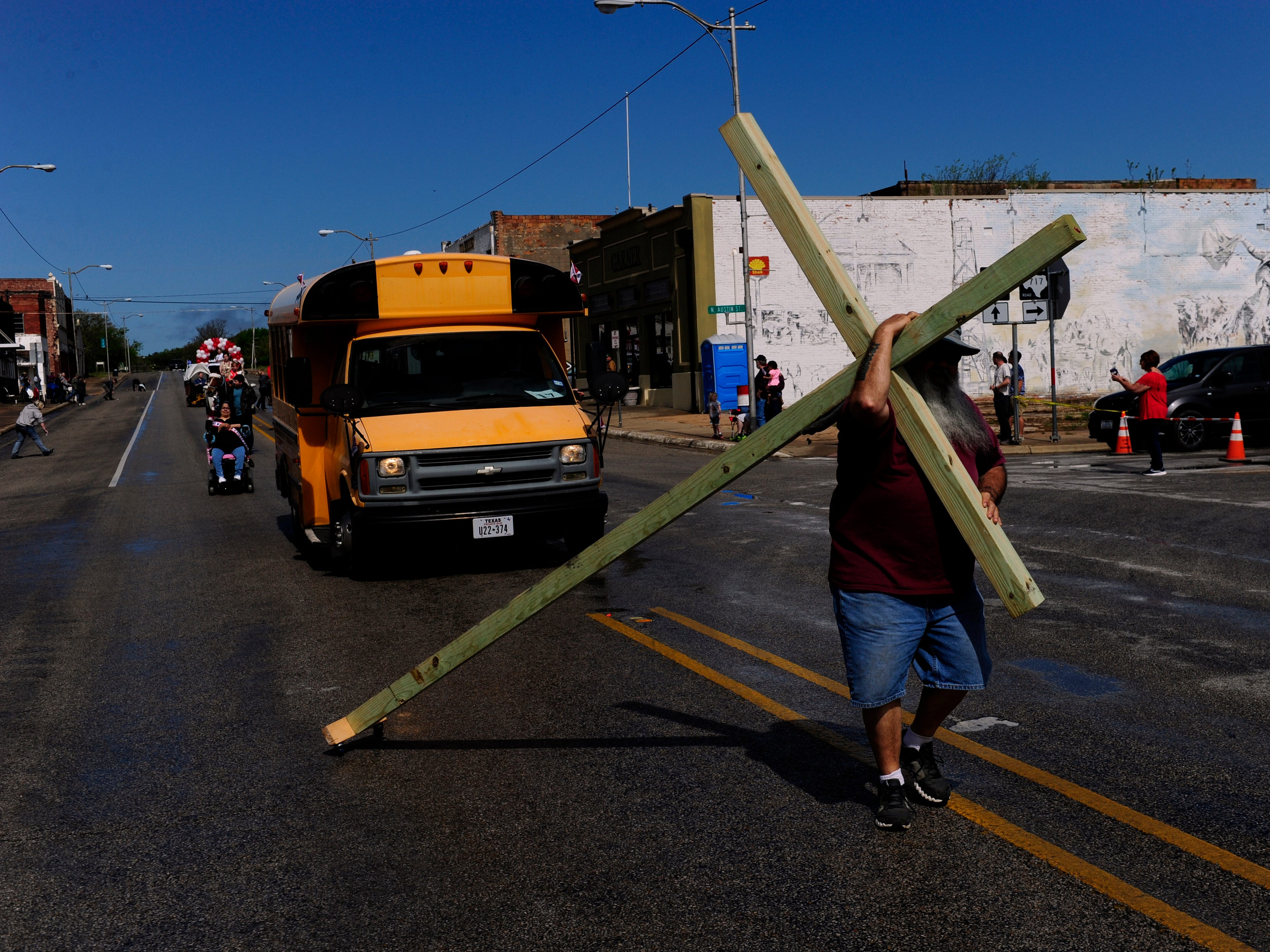 Brady Bowles of His Hands Ministries drags a cross during the centennial parade for Ranger April 6, 2019. Rain scared off some parade attendees and participants, but clearing skies eventually only delayed it for forty-five minutes.