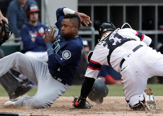Seattle Mariners' Tim Beckham, left, scores on a three-run double by Daniel Vogelbach as Chicago White Sox catcher Welington Castillo misses the ball during the third inning of a baseball game in Chicago, Sunday, April 7, 2019.