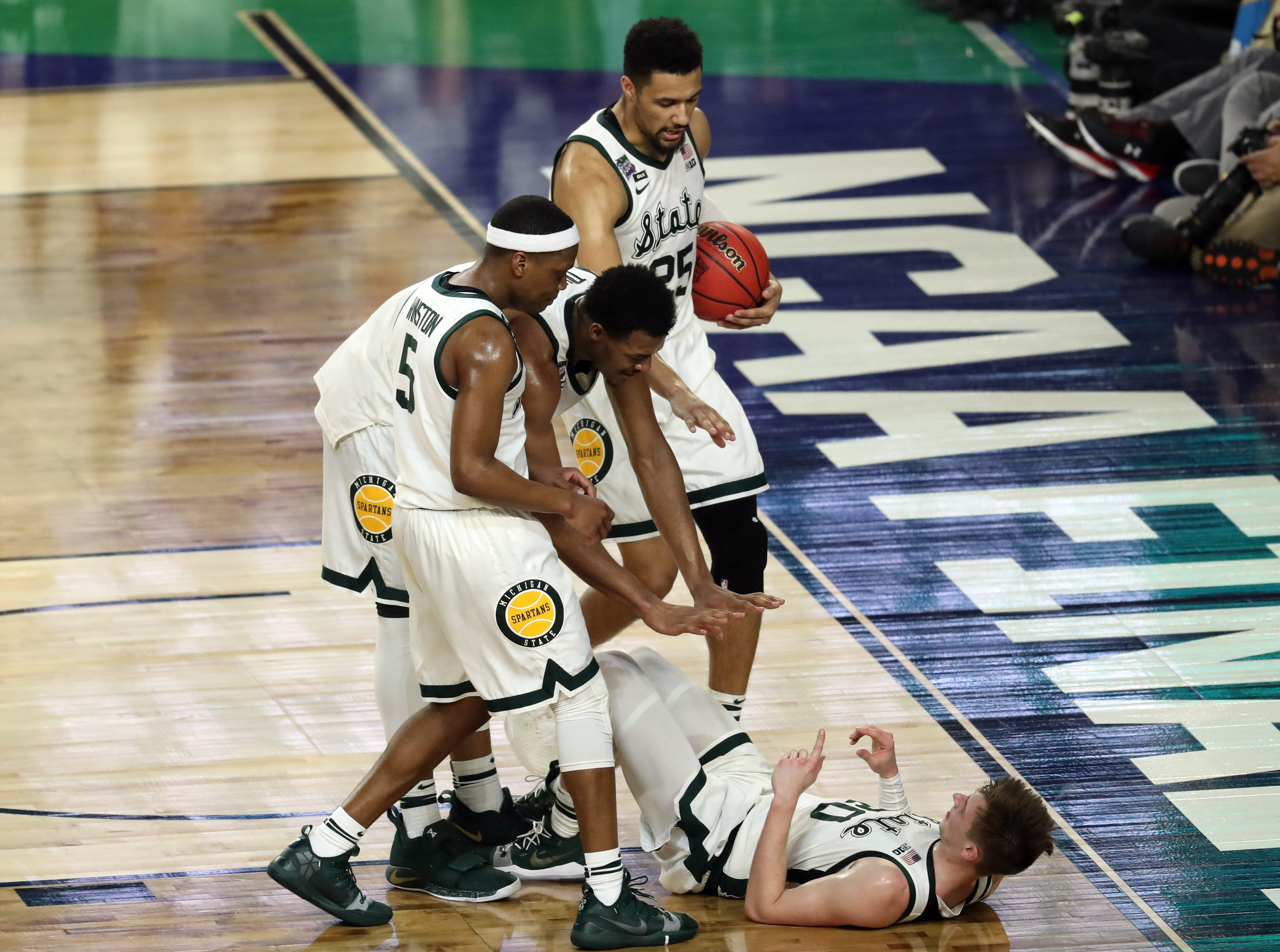 Apr 6, 2019; Minneapolis, MN, USA; Michigan State Spartans guard Cassius Winston (5) and teammates help guard Matt McQuaid (20) up during the first half against the Texas Tech Red Raiders in the semifinals of the 2019 men's Final Four at US Bank Stadium. Mandatory Credit: Brace Hemmelgarn-USA TODAY Sports
