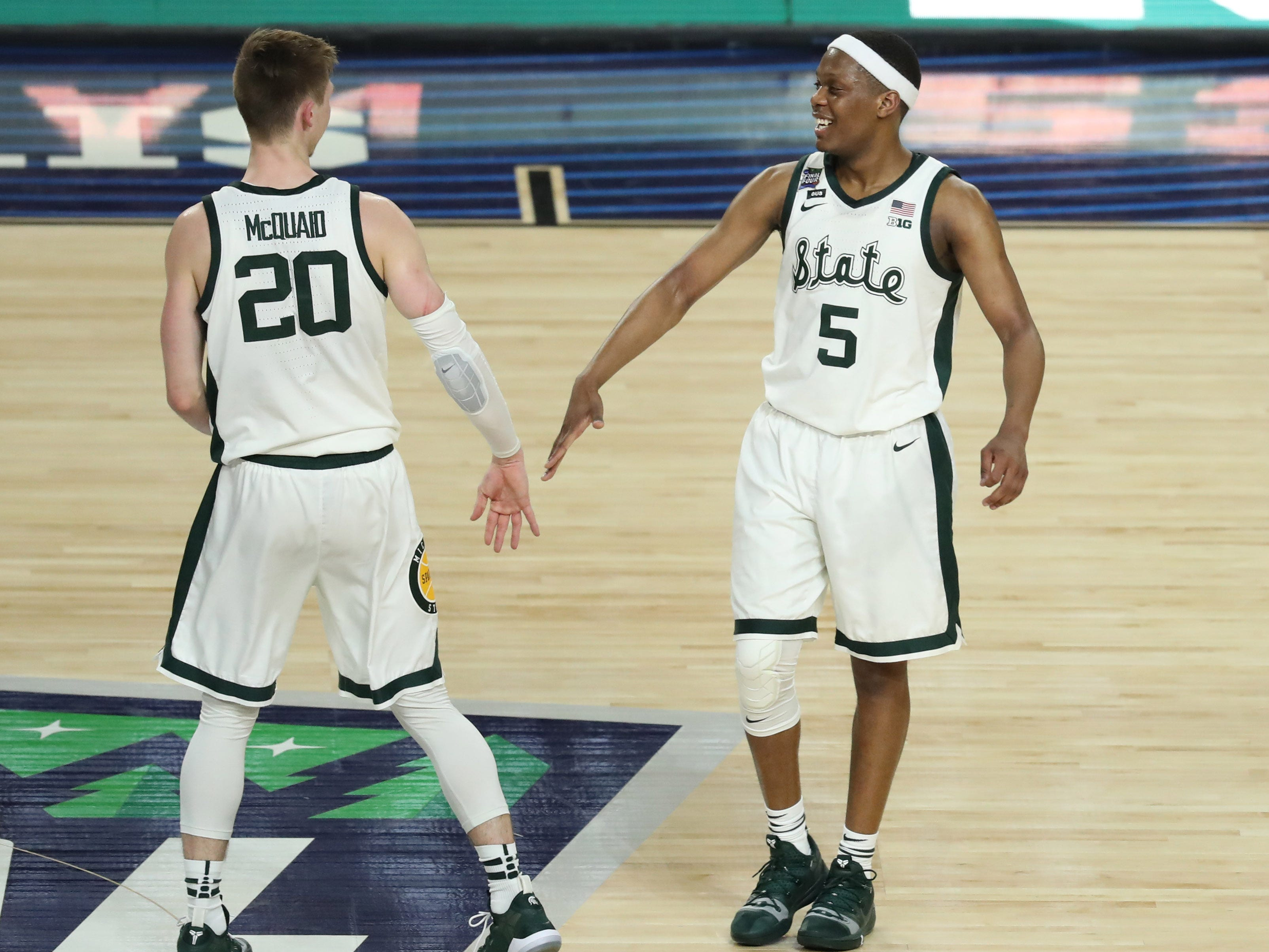 Apr 6, 2019; Minneapolis, MN, USA; Michigan State Spartans guard Matt McQuaid (20) and guard Cassius Winston (5) celebrate during the first half against the Texas Tech Red Raiders in the semifinals of the 2019 men's Final Four at US Bank Stadium. Mandatory Credit: Brace Hemmelgarn-USA TODAY Sports