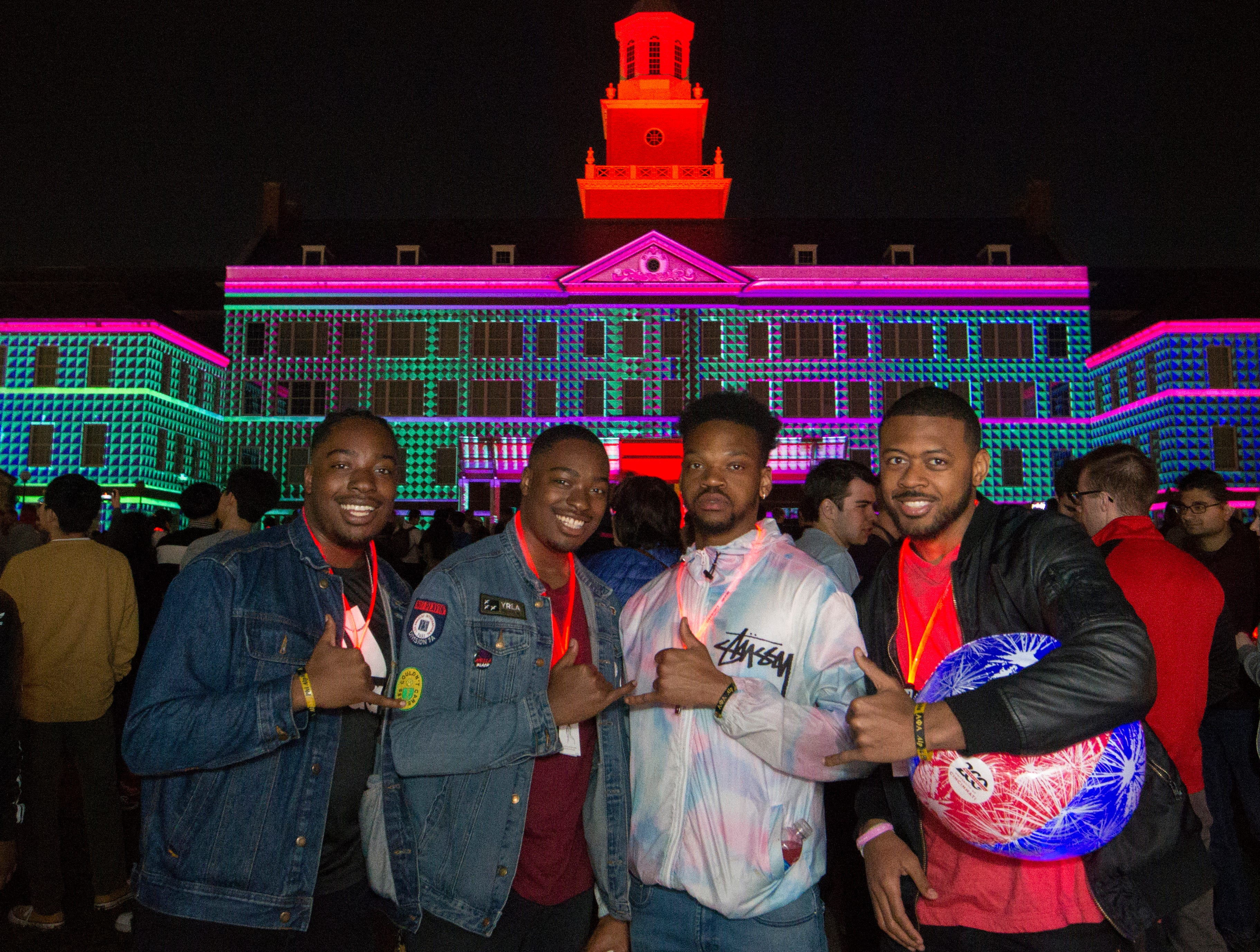 Left to right UC students Kaleb Kinebrew, Kameron Kinebrew, Denzel Welch and Dwayne Johnson posed for a photo with Momentum Projection-Mapping Light Show Saturday April 6, 2019 at McMicken Commons on the campus of the University of Cincinnati. University of Cincinnati/Joseph Fuqua II