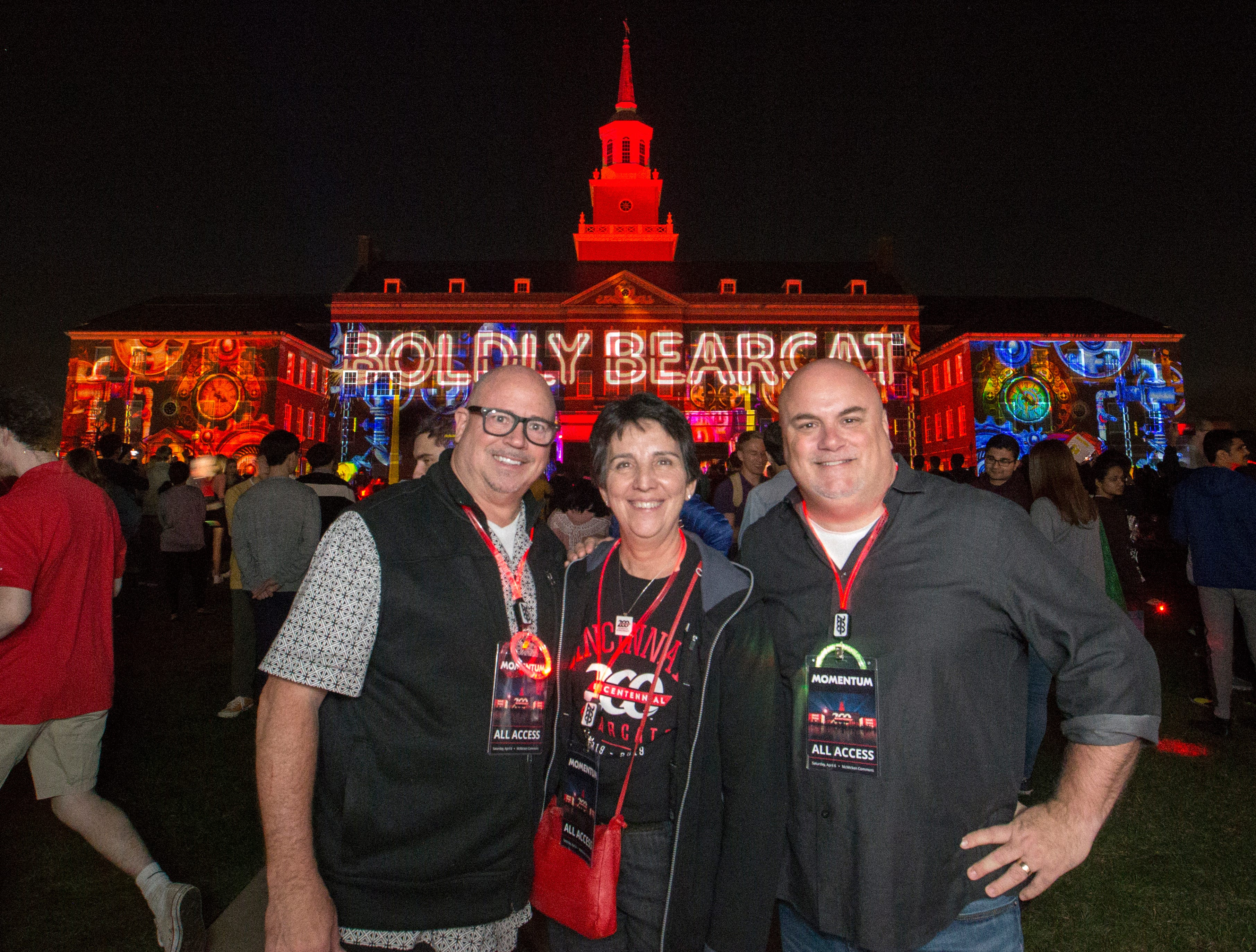 Left to right Steve McGowan, Kimberlee J. Dobbs UC Bicentennial Co-Chair and Dan Reynolds posed with Boldly Bearcat illuminating on McMicken Hall during Community Day to celebrate UC's Bicentennial Saturday April 6, 2019 at McMicken Commons on the campus of the University of Cincinnati. Steve McGowan and Dan Reynolds are co-owner of Brave Berlin. University of Cincinnati/Joseph Fuqua II
