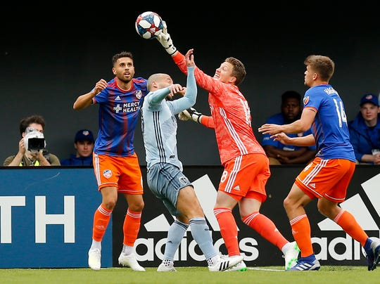 FC Cincinnati goalkeeper Spencer Richey (18) slaps away a shot in the first half of the MLS match between FC Cincinnati and Sporting Kansas City at Nippert Stadium in Cincinnati on Sunday, April 7, 2019. FC Cincinnati and Sporting Kansas City played to a 1-1 tie.
