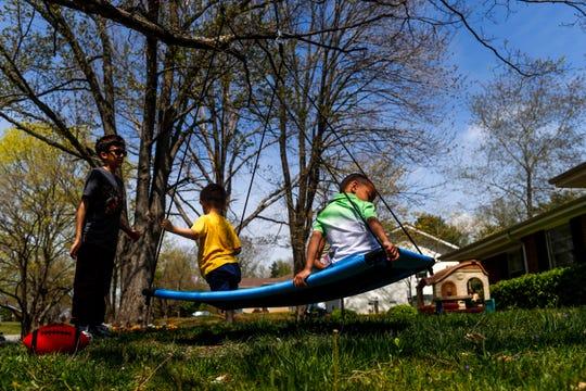 Atticus Webber, 4, plays on the swing with his neighbors Luke Hobbs, 4, center, and Ashton Hobbs, 11, left, at the Webber household in Clarksville, Tenn., on Saturday, April 6, 2019.