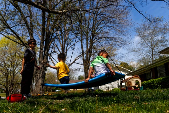 Atticus Webber, 4, plays on the swing with his neighbors Luke Hobbs, 4, center, and Ashton Hobbs, 11, left, at the Webber household in Clarksville, Tenn., on Saturday, April 6, 2019.