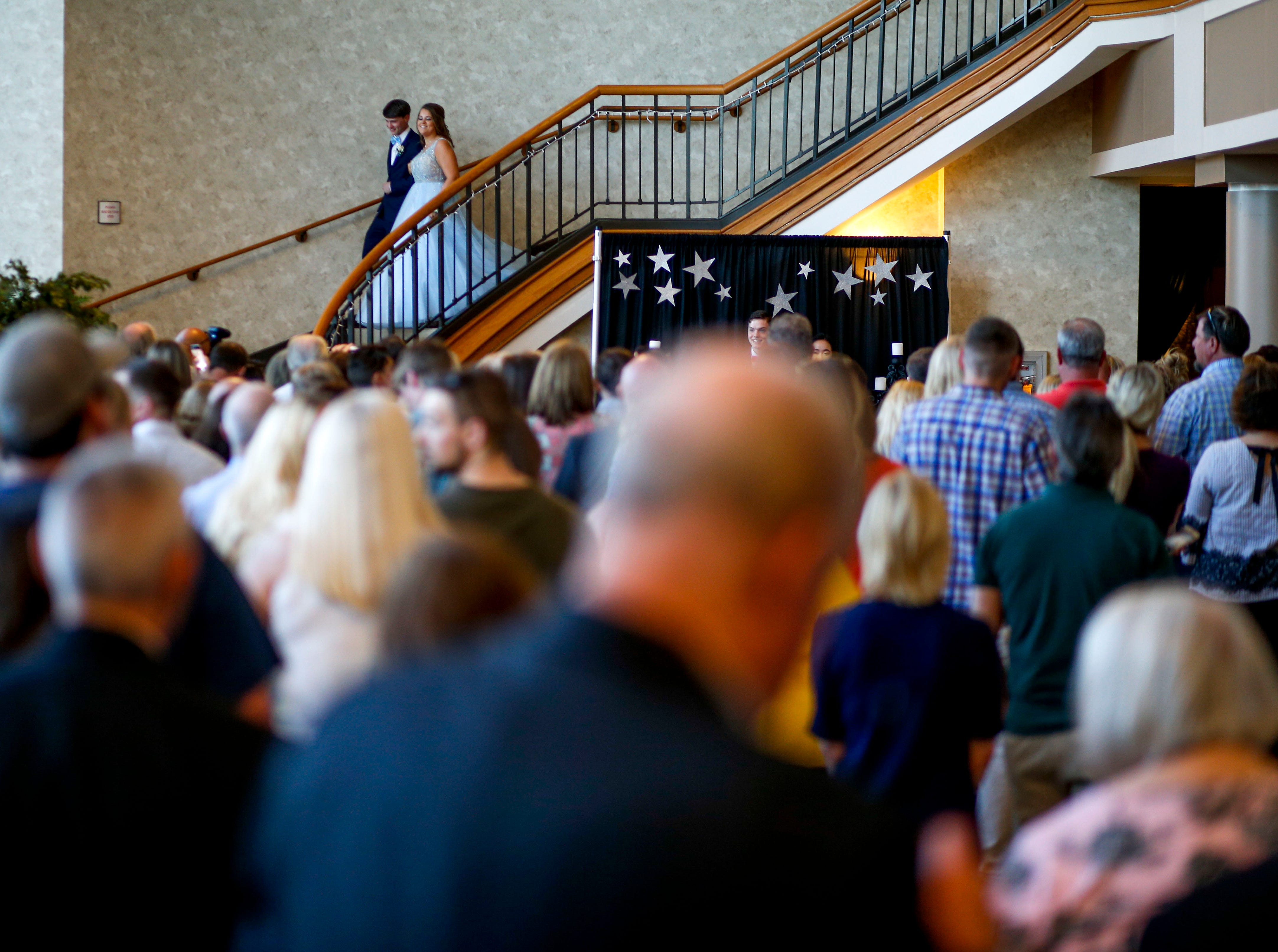 Students descend a staircase in front of friends and family during Clarksville Academy's 2019 prom at The Bruce Convention Center in Hopkinsville, Ky., on Saturday, April 6, 2019.