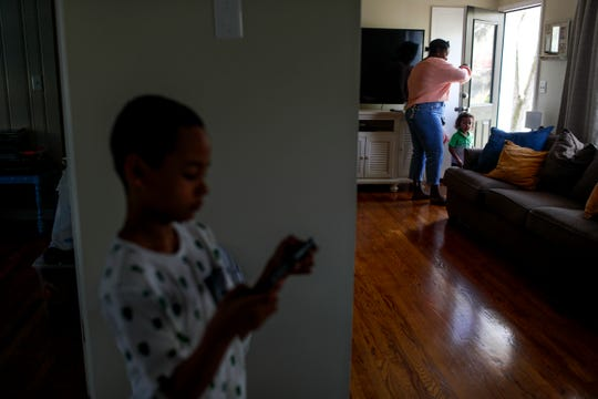 Shanesse Webber, grabs her youngest son Ezra, 2, before he runs outside to put his shoes on while Kingston Webber, 9, plays Dragon Ball Z on his Nintendo Switch at the Webber household in Clarksville, Tenn., on Saturday, April 6, 2019.
