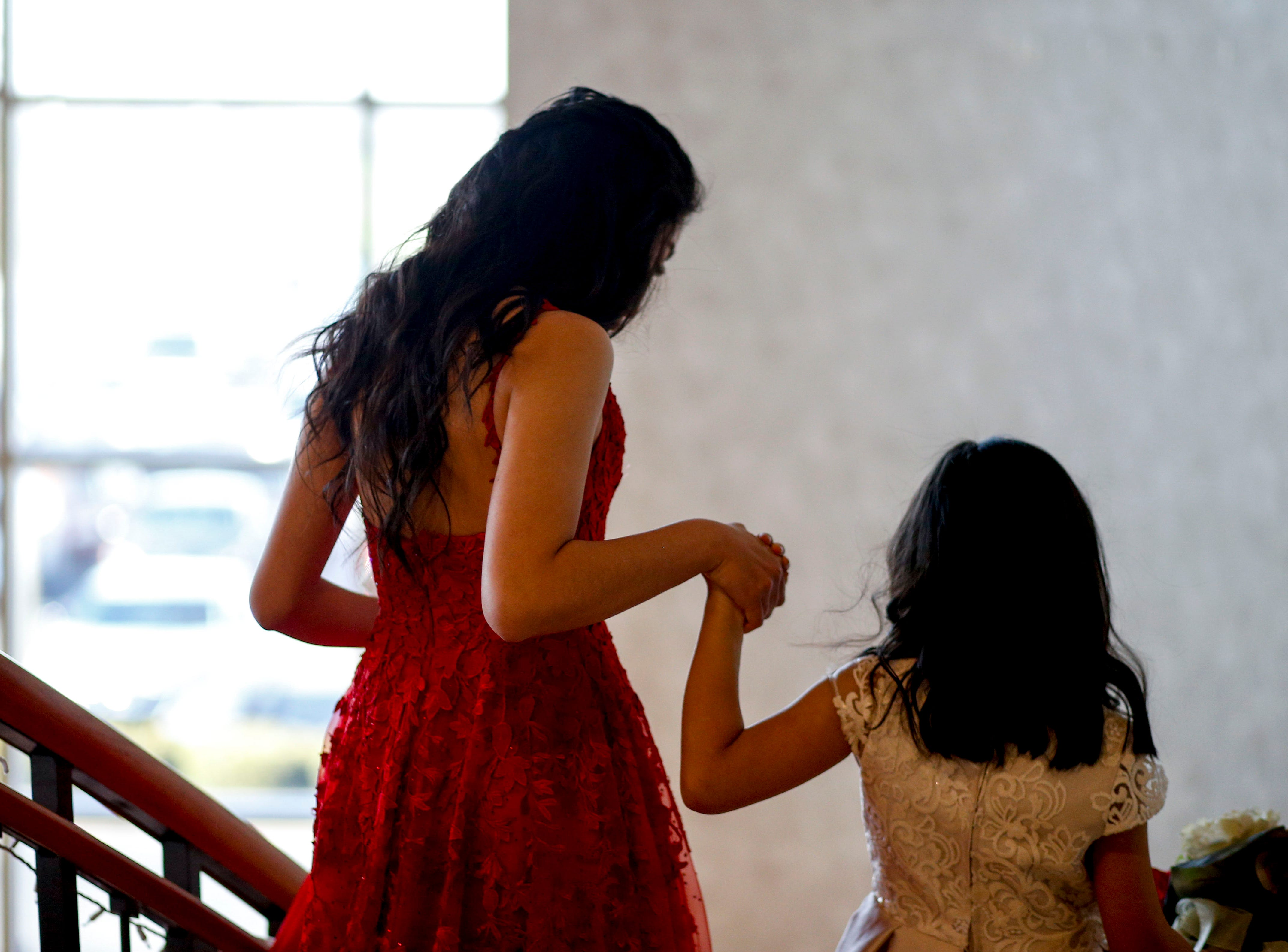 A student is escorted down the staircase in front of friends and family during Clarksville Academy's 2019 prom at The Bruce Convention Center in Hopkinsville, Ky., on Saturday, April 6, 2019.