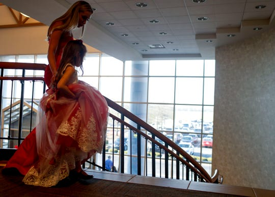 A senior walks with her escort down the flight of stairs in front of friends and family for photos during Clarksville Academy's 2019 prom at The Bruce Convention Center in Hopkinsville, Ky., on Saturday, April 6, 2019.
