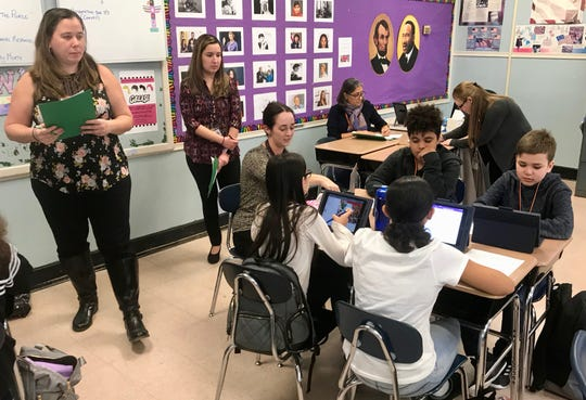 McManus Middle School teachers Brenda Kaneaster and Jennifer Fernandes observe as Aimee Bass works with students during instructional rounds.
