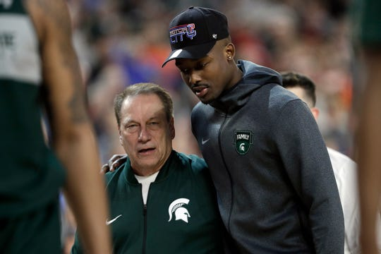 Michigan State head coach Tom Izzo walks with injured guard Joshua Langford during a practice session for the Final Four, April 5, 2019, in Minneapolis.