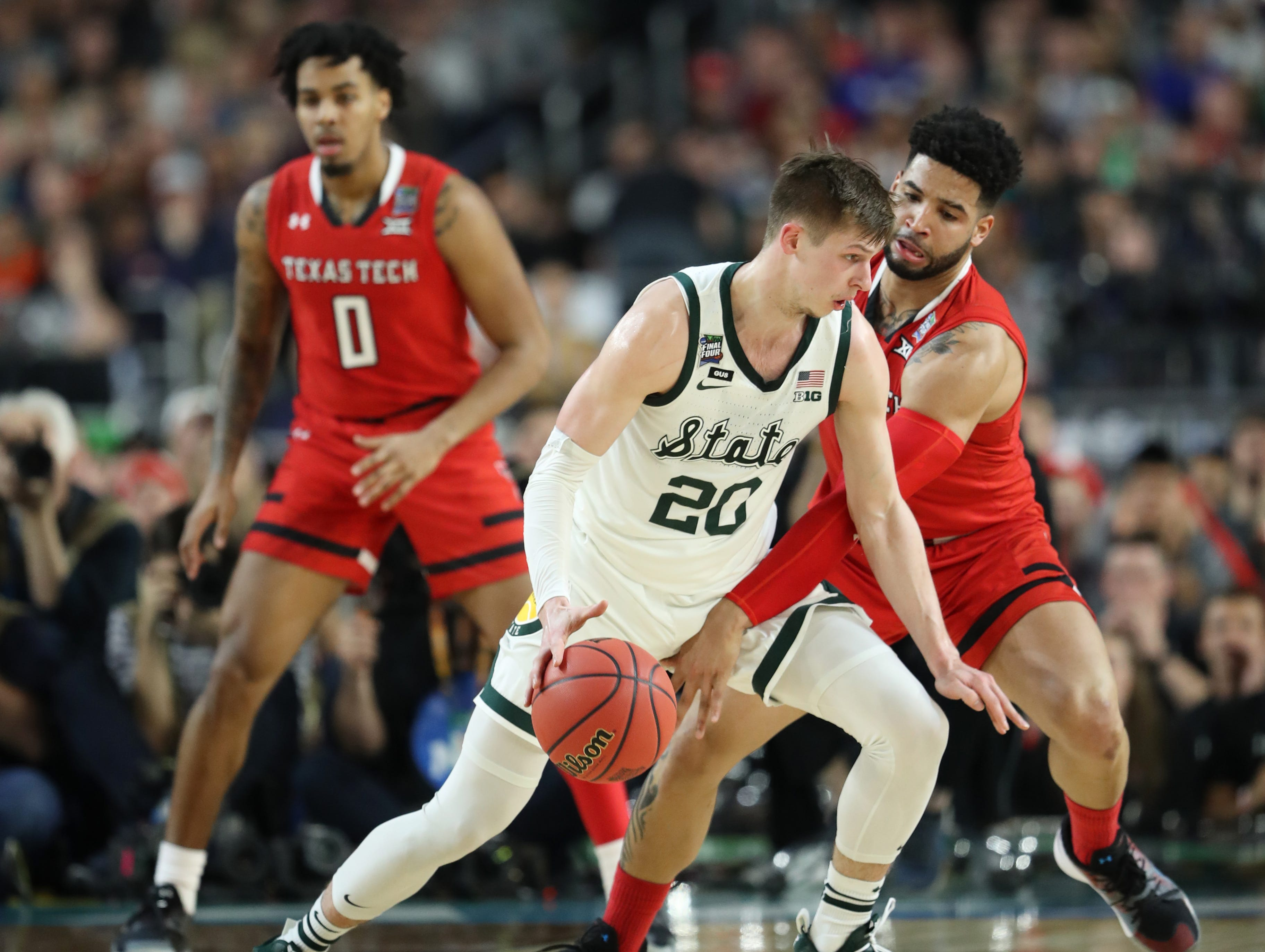 Michigan State guard Matt McQuaid (20) attempts to move the ball around Texas Tech guard Brandone Francis (1) during the first half of the Spartan's Final Four game at U.S. Bank Stadium in Minneapolis, Minnesota on Saturday, April 06, 2019.