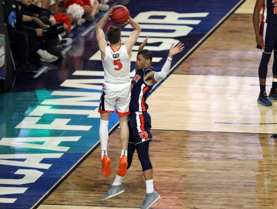Virginia guard Kyle Guy is fouled by Auburn guard Samir Doughty in the final second of the Final Four national semifinal, Saturday, April 6, 2019, in Minneapolis.