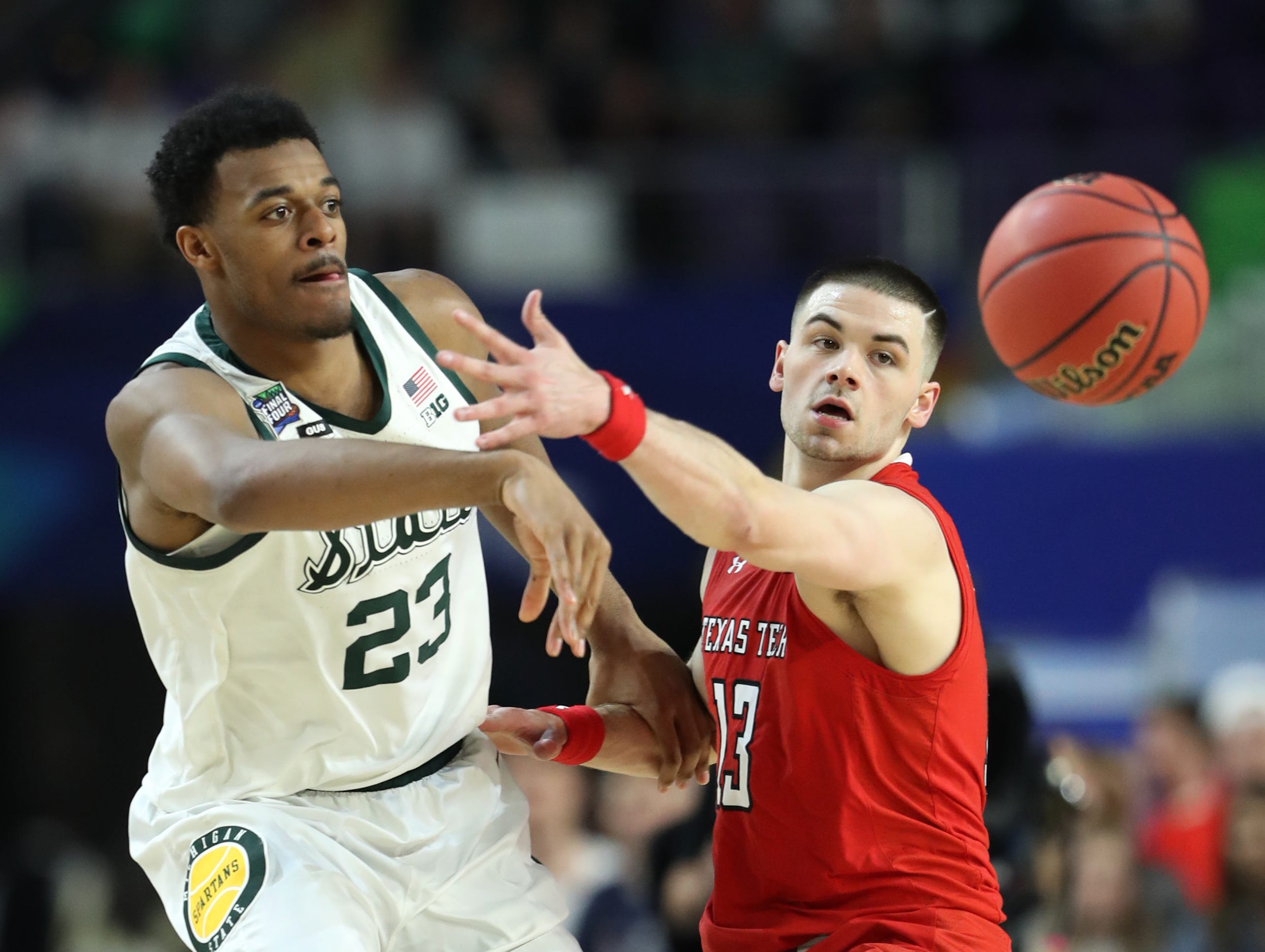 Michigan State forward Xavier Tillman (23) passes the ball around guard Matt Mooney (13) during the first half of the Spartan's Final Four game at U.S. Bank Stadium in Minneapolis, Minnesota on Saturday, April 06, 2019.