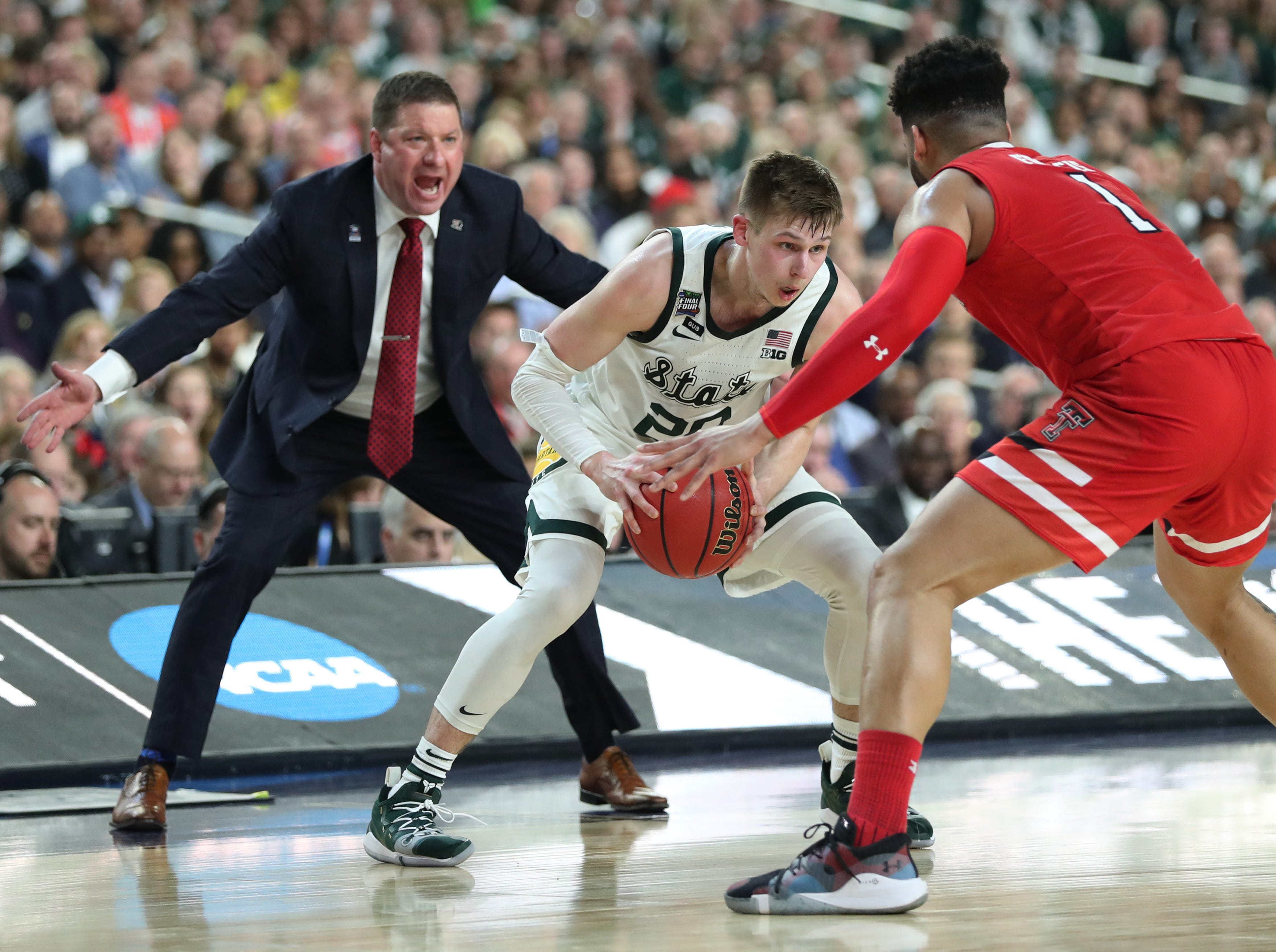Texas Tech head coach Chris Beard is seen as Michigan State guard Matt McQuaid (20) looks to move the ball around Texas Tech guard Brandone Francis (1) in the first half of the Spartan's Final Four game at U.S. Bank Stadium in Minneapolis, Minnesota on Saturday, April 06, 2019.