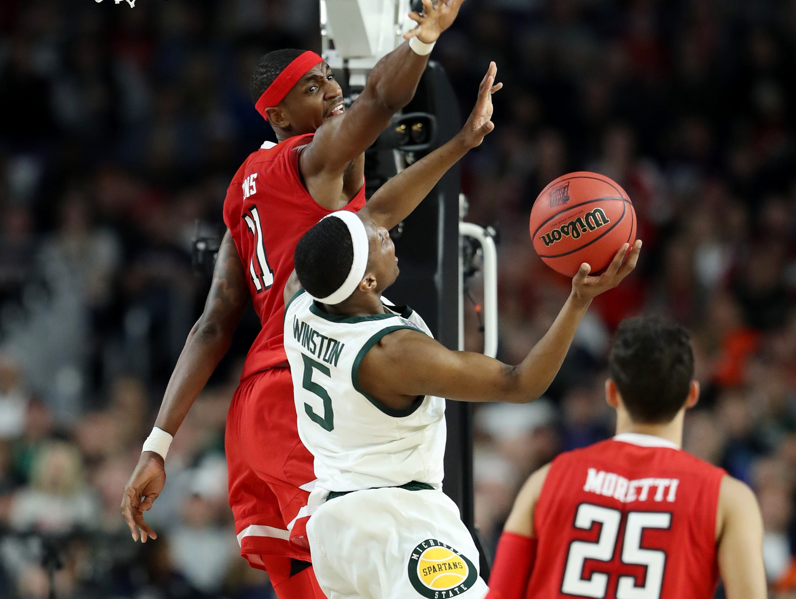 Michigan State guard Cassius Winston (5) looks to shoot the ball around Texas Tech forward Tariq Owens (11) in the first half of the Spartan's Final Four game at U.S. Bank Stadium in Minneapolis, Minnesota on Saturday, April 06, 2019.