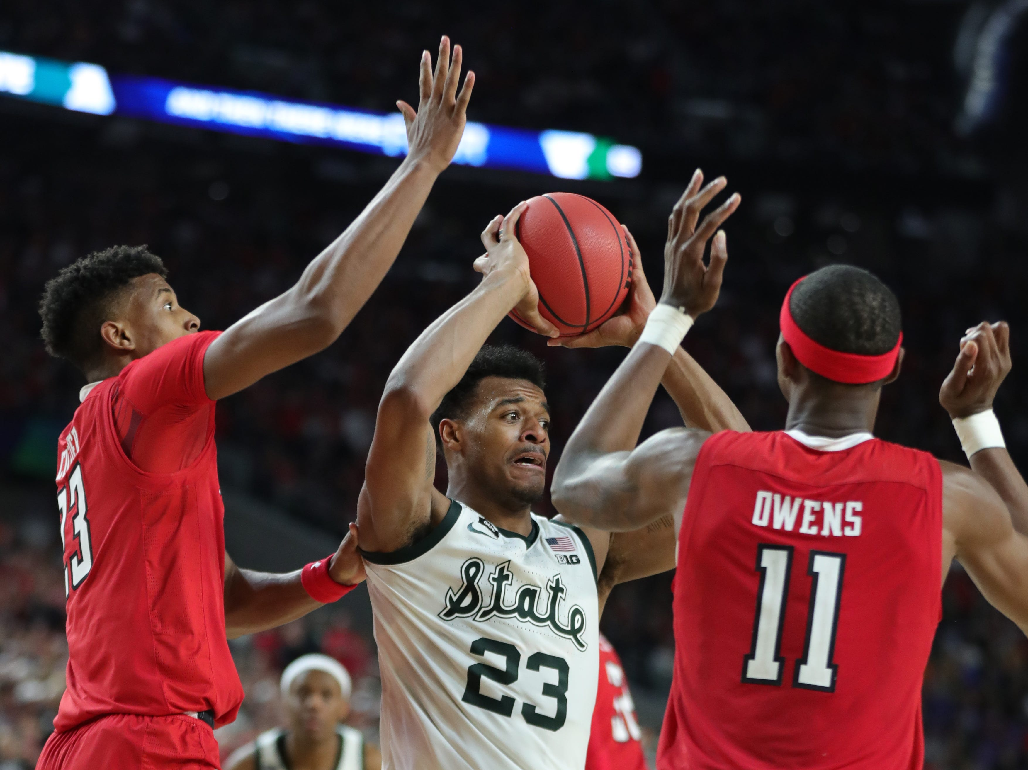 Michigan State forward Xavier Tillman (23) looks to pass the ball around Texas Tech guard Jarrett Culver (23) and forward Tariq Owens (11) in the second half of the Final Four game at U.S. Bank Stadium in Minneapolis, Minnesota on Saturday, April 06, 2019.