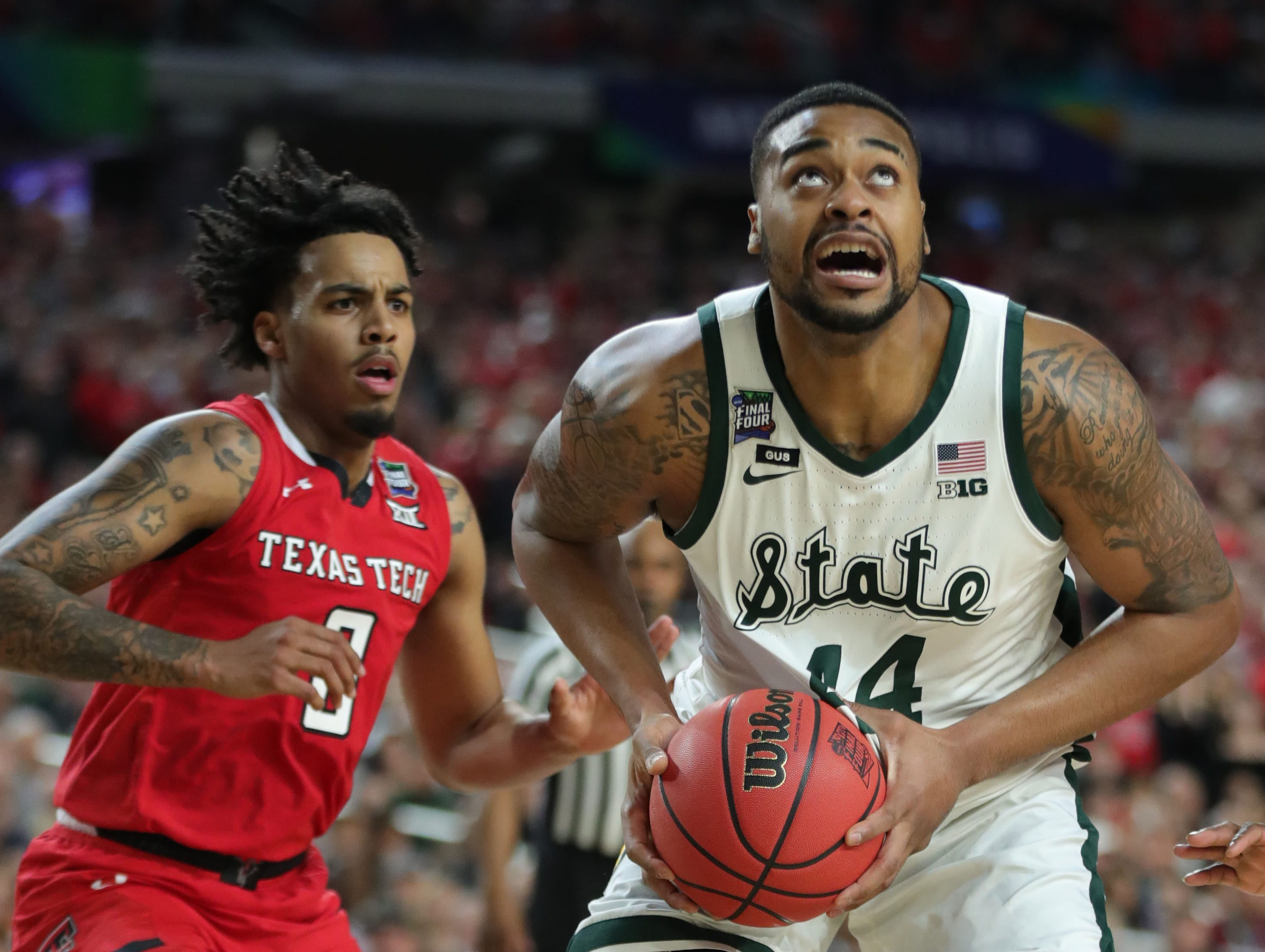 Michigan State Nick Ward (44) moves the ball around Texas Tech guard Kyler Edwards (0) in the second half of the Final Four game at U.S. Bank Stadium in Minneapolis, Minnesota on Saturday, April 06, 2019.