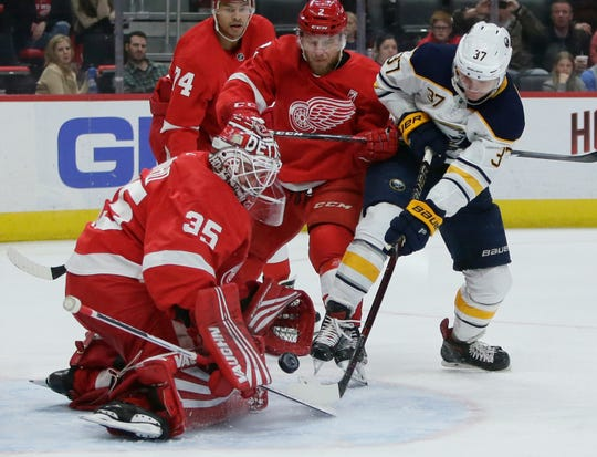 Red Wings goaltender Jimmy Howard stops a shot on goal by Sabres center Casey Mittelstadt with Wings defenseman Joe Hicketts helping defend during the first period Saturday in Detroit.
