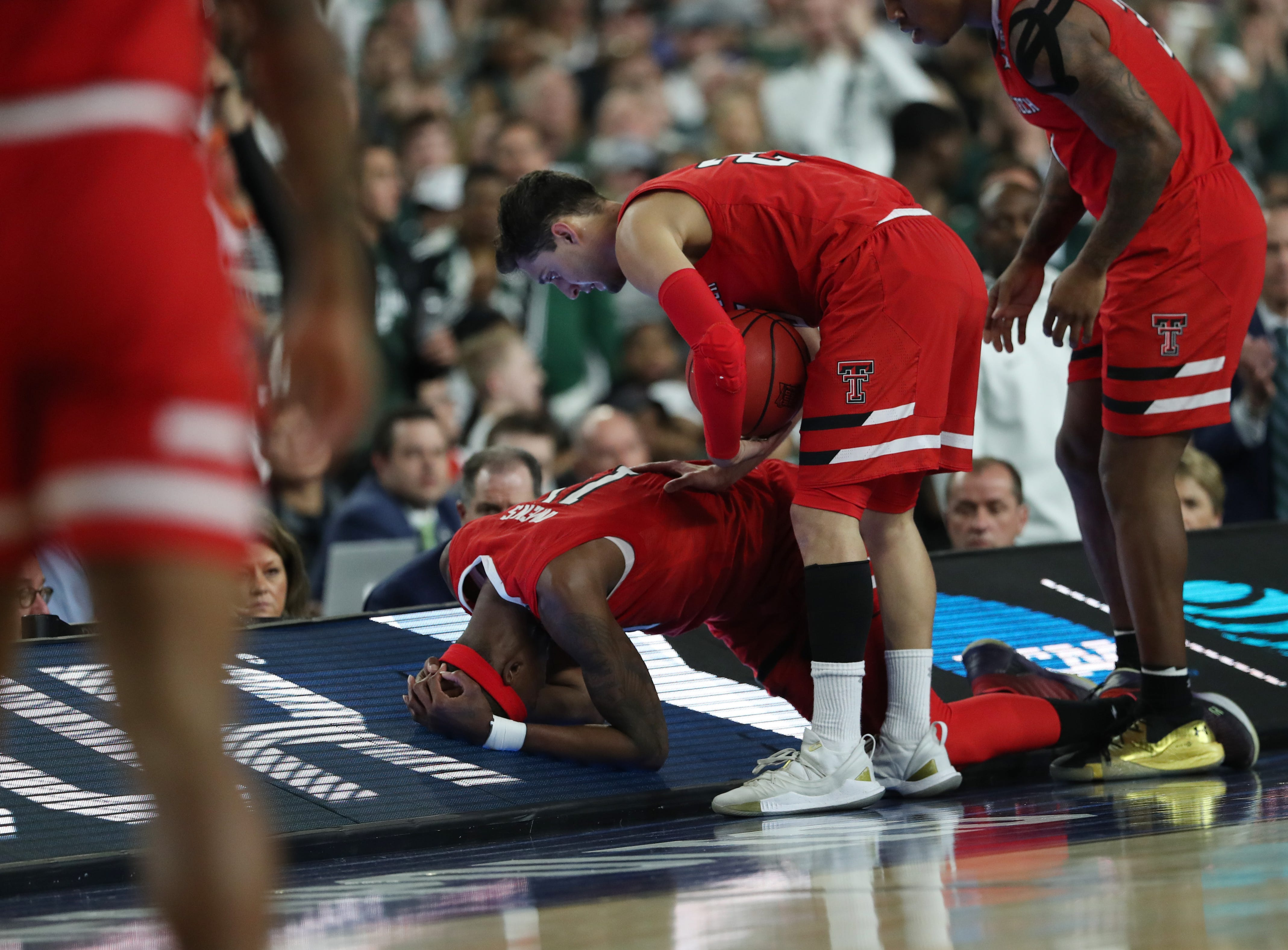 Texas Tech forward Tariq Owens (11) holds his head after an injury during the first half of the Final Four game against Michigan State at U.S. Bank Stadium in Minneapolis, Minnesota on Saturday, April 06, 2019.