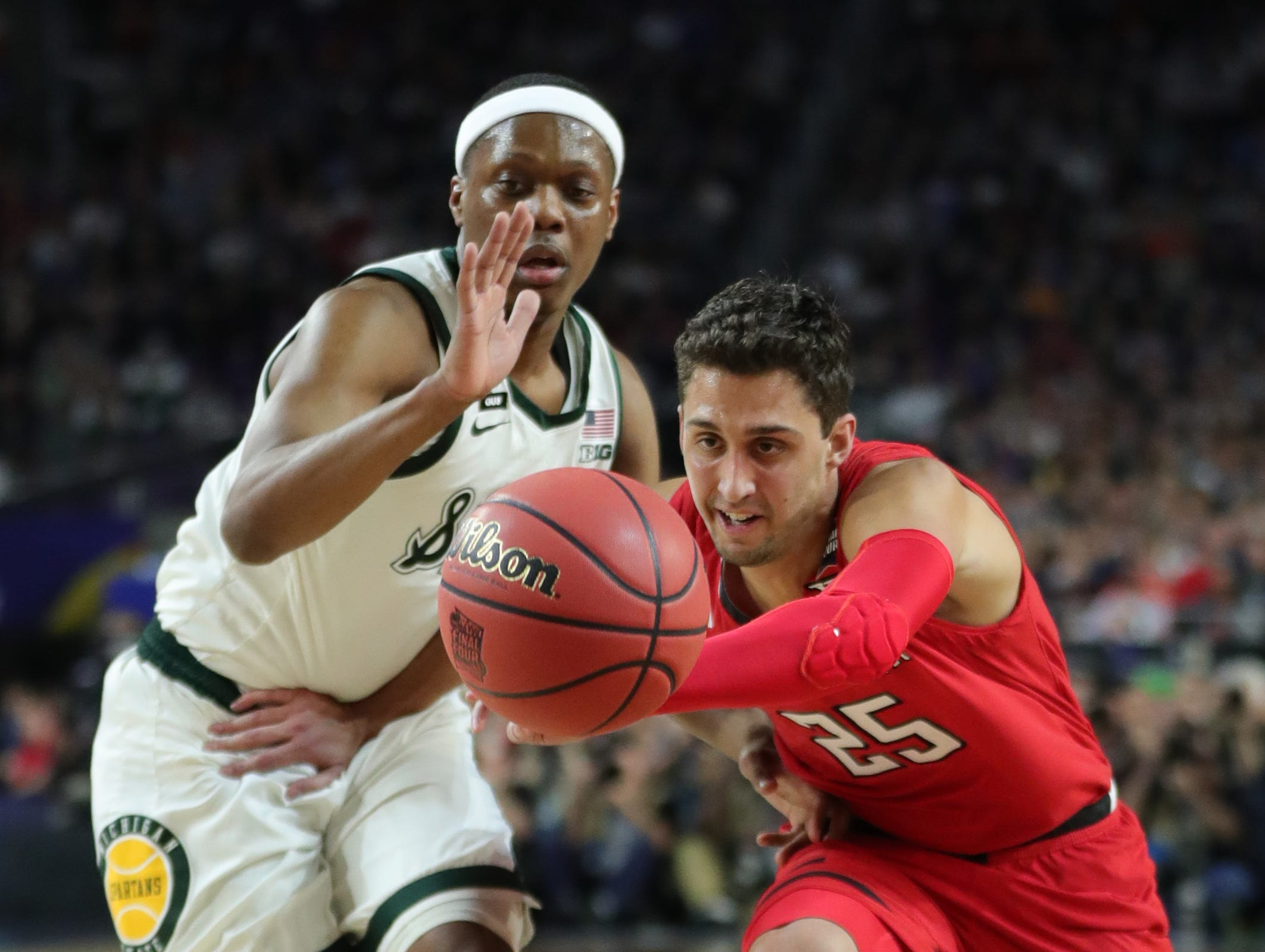 Michigan State guard Cassius Winston (5) and guard Davide Moretti (25) run down the ball in the first half of their Final Four game at U.S. Bank Stadium in Minneapolis, Minnesota on Saturday, April 06, 2019.