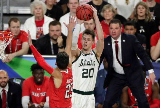 Michigan State guard Matt McQuaid (20) shoots over Texas Tech guard Davide Moretti during the first half in the semifinals of the Final Four NCAA college basketball tournament, Saturday, April 6, 2019, in Minneapolis.