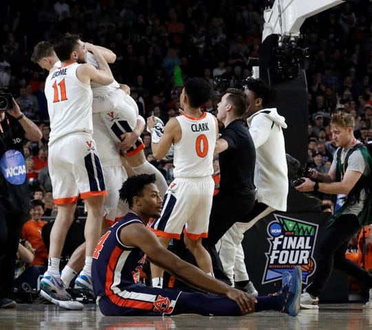 Auburn's Anfernee McLemore (24) reacts on the floor as Virginia players celebrate after defeating Auburn 63-62.