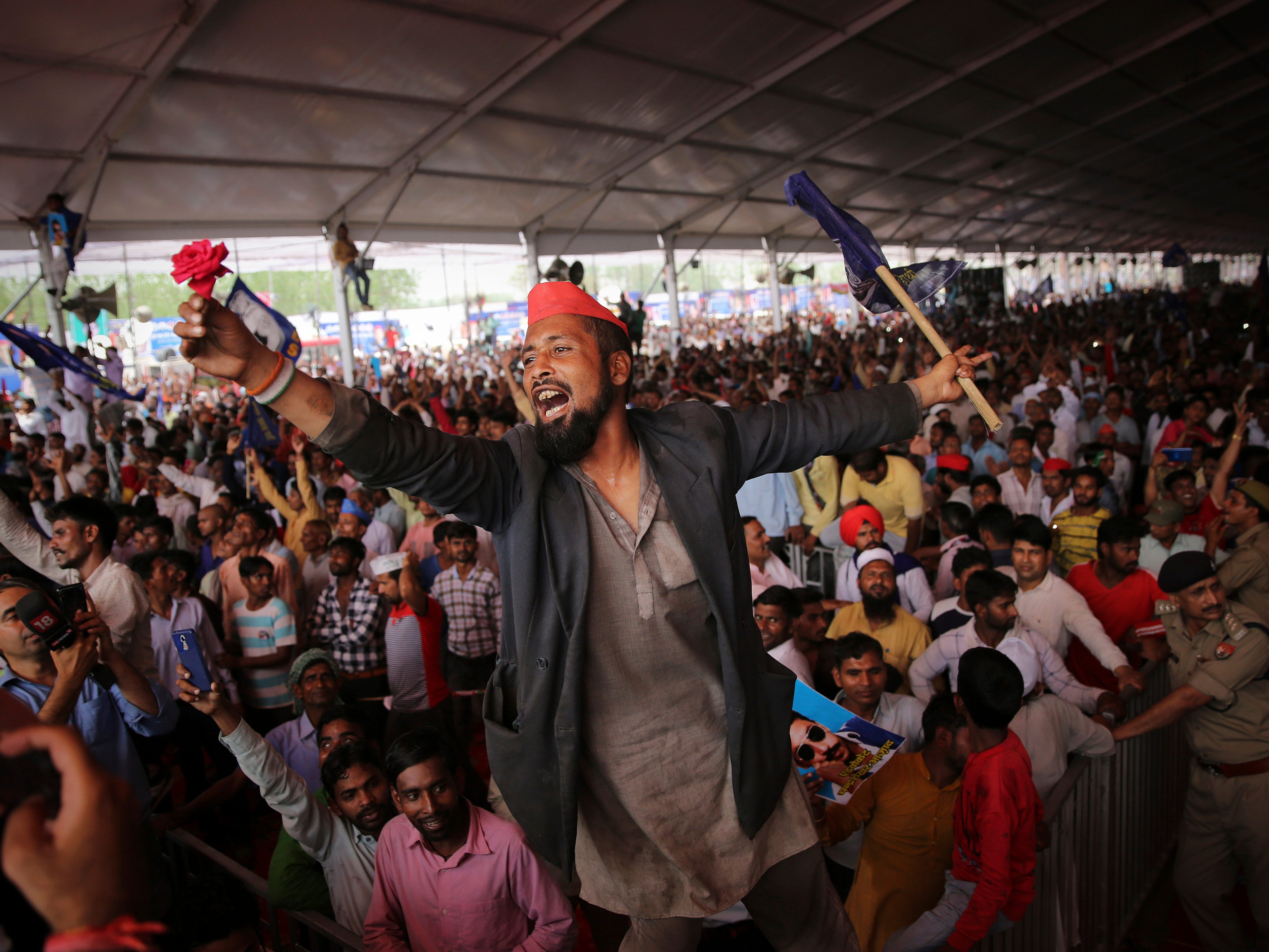 A man cheers holding a flower in hand as supporters of Bahujan Samaj Party (BSP), Samajwadi Party (SP) and Rashtriya Lok Dal (RLD) gather during an election rally in Deoband, Uttar Pradesh, India, Sunday, April 7, 2019. Political archrivals in India's most populous state rallied together Sunday, asking voters to support a new alliance created with the express purpose of defeating Prime Minister Narendra Modi's ruling Hindu nationalist Bharatiya Janata Party.