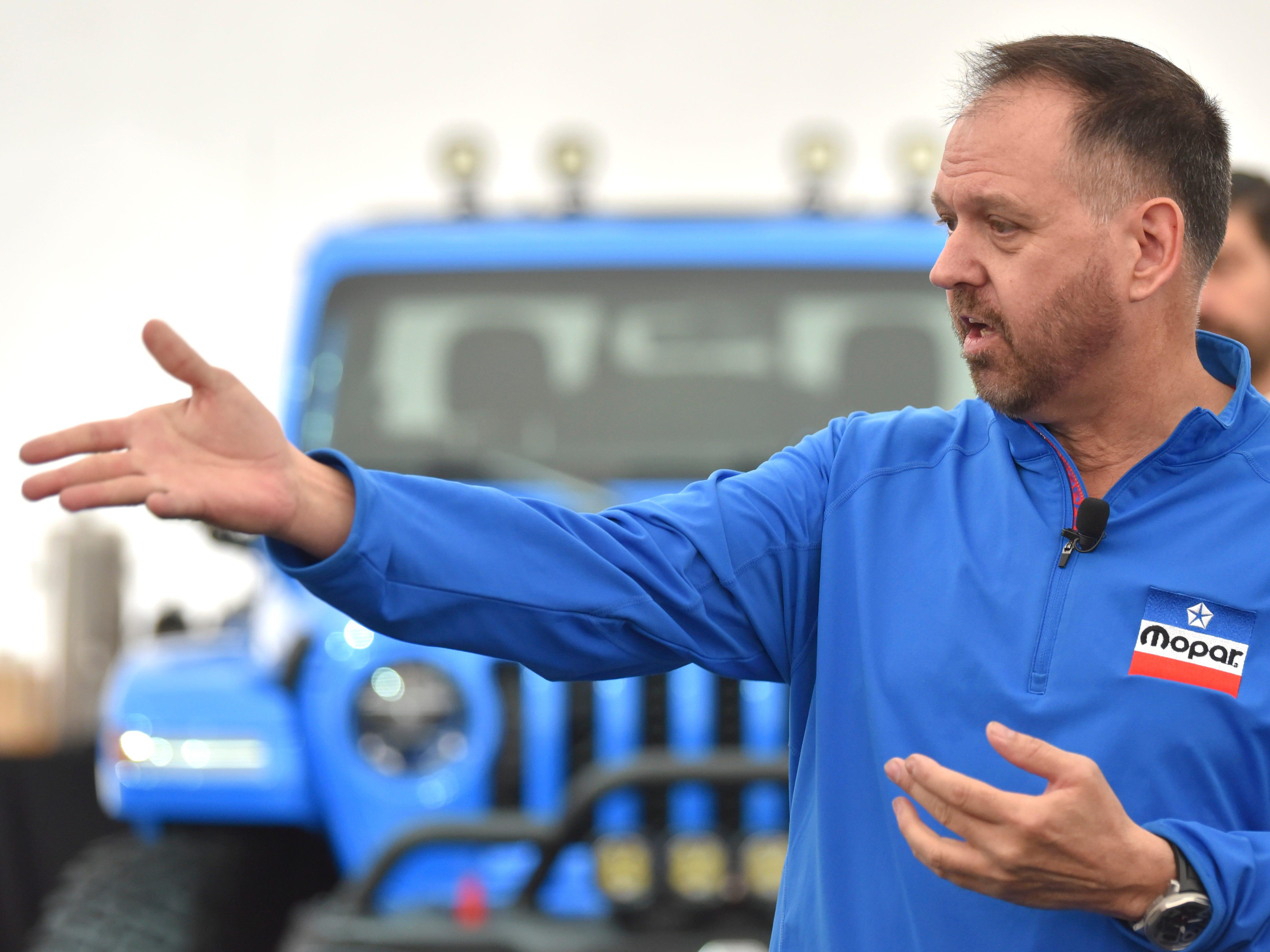 Joe Dehner, head of Ram & Mopar Design, speaks in front of the Jeep J6 concept in Brilliant Metallic Blue.