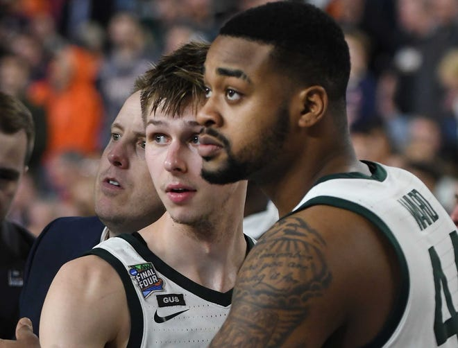 Michigan State's Matt McQuaid and Nick Ward hug as they come out of the game near the end of the second half. Texas Tech defeated Michigan State 61-51.
