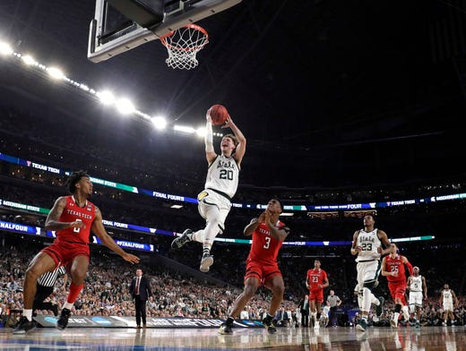 Michigan State guard Matt McQuaid (20) drives to the basket over Texas Tech's Kyler Edwards, left, and Deshawn Corprew (3) during the first half.