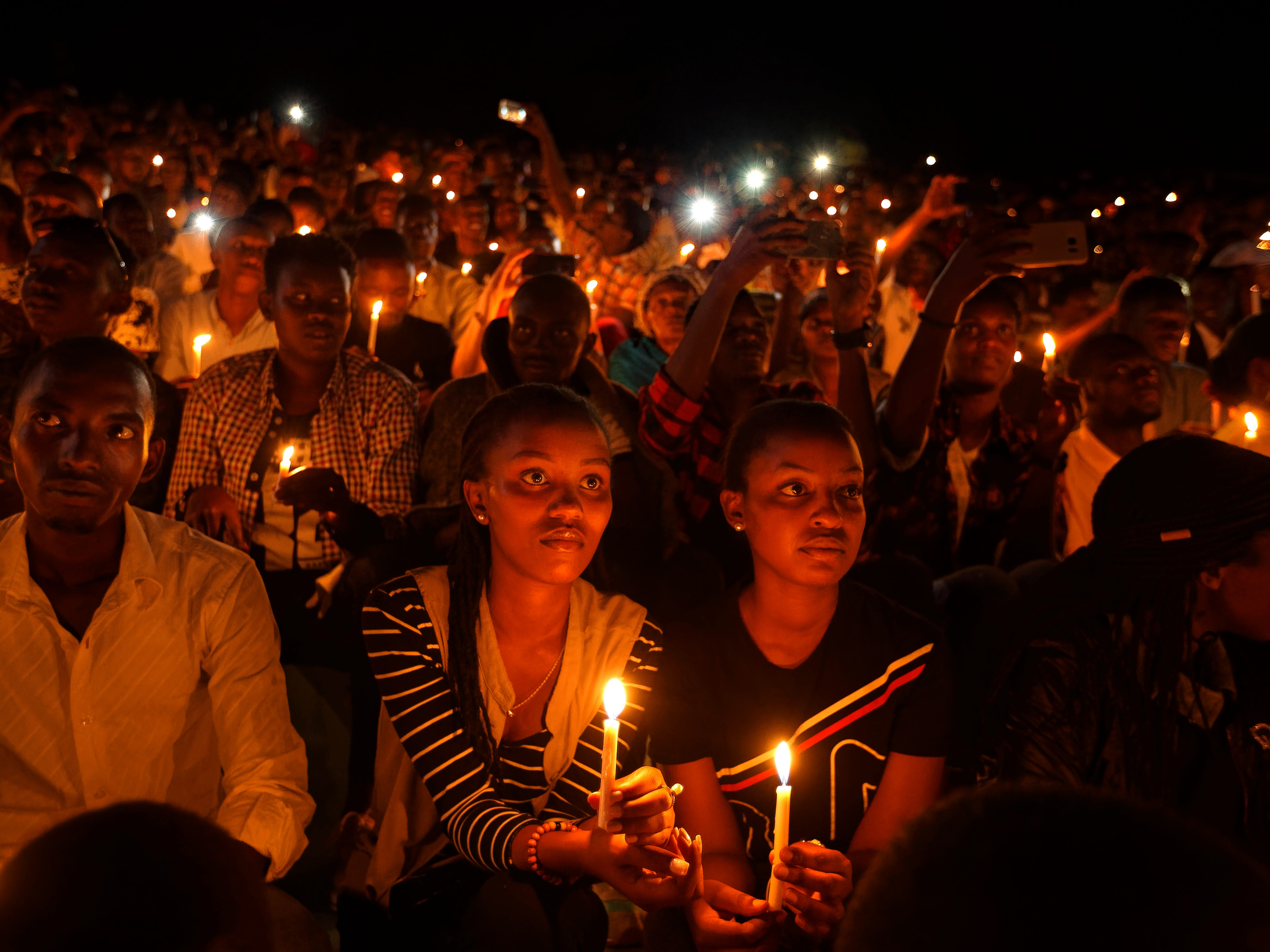 Rwandans sitting in the stands hold candles at a vigil during the memorial service at Amahoro stadium in the capital Kigali, Rwanda Sunday, April 7, 2019. Rwanda is commemorating the 25th anniversary of when the country descended into an orgy of violence in which some 800,000 Tutsis and moderate Hutus were massacred by the majority Hutu population over a 100-day period in what was the worst genocide in recent history.