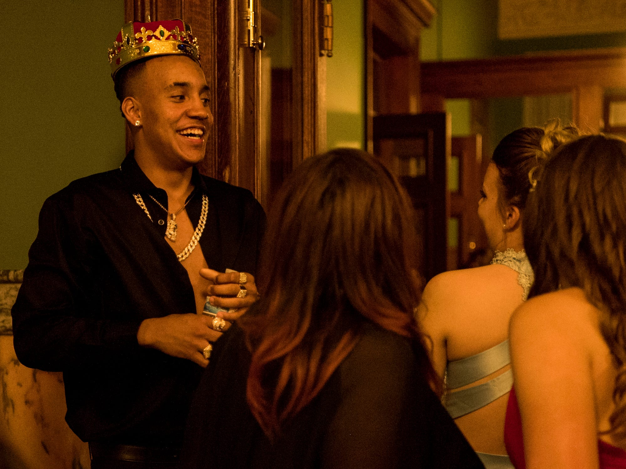 Donovan McNeal jokingly tries on the prom king crown before taking photos with friends at the Old Vanderburgh County Courthouse in downtown Evansville, Ind., Saturday, April 6, 2019.