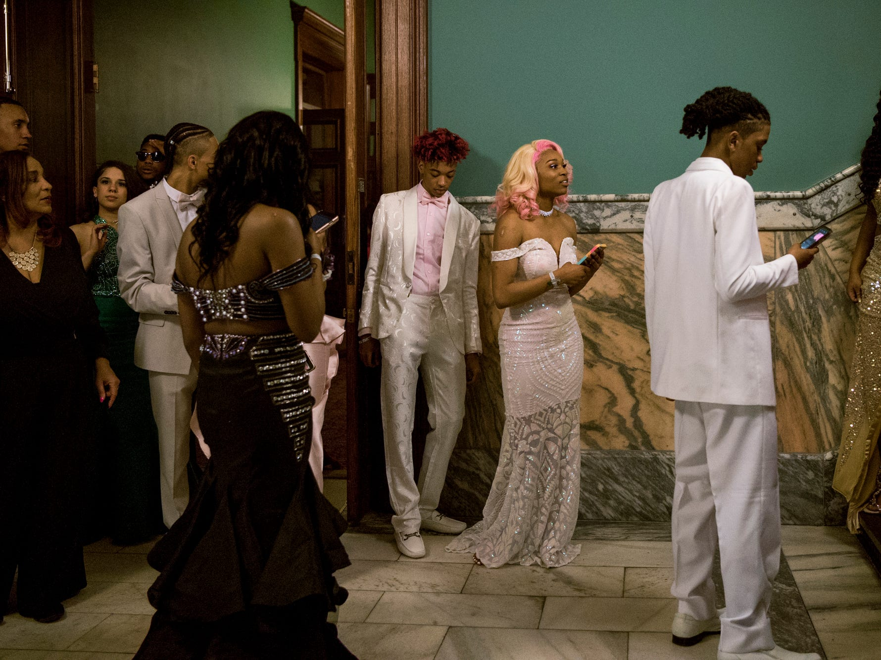 Bosse High School students prepare to line up on the stairs for a group photos during prom at the Old Vanderburgh County Courthouse in downtown Evansville, Ind., Saturday, April 6, 2019.