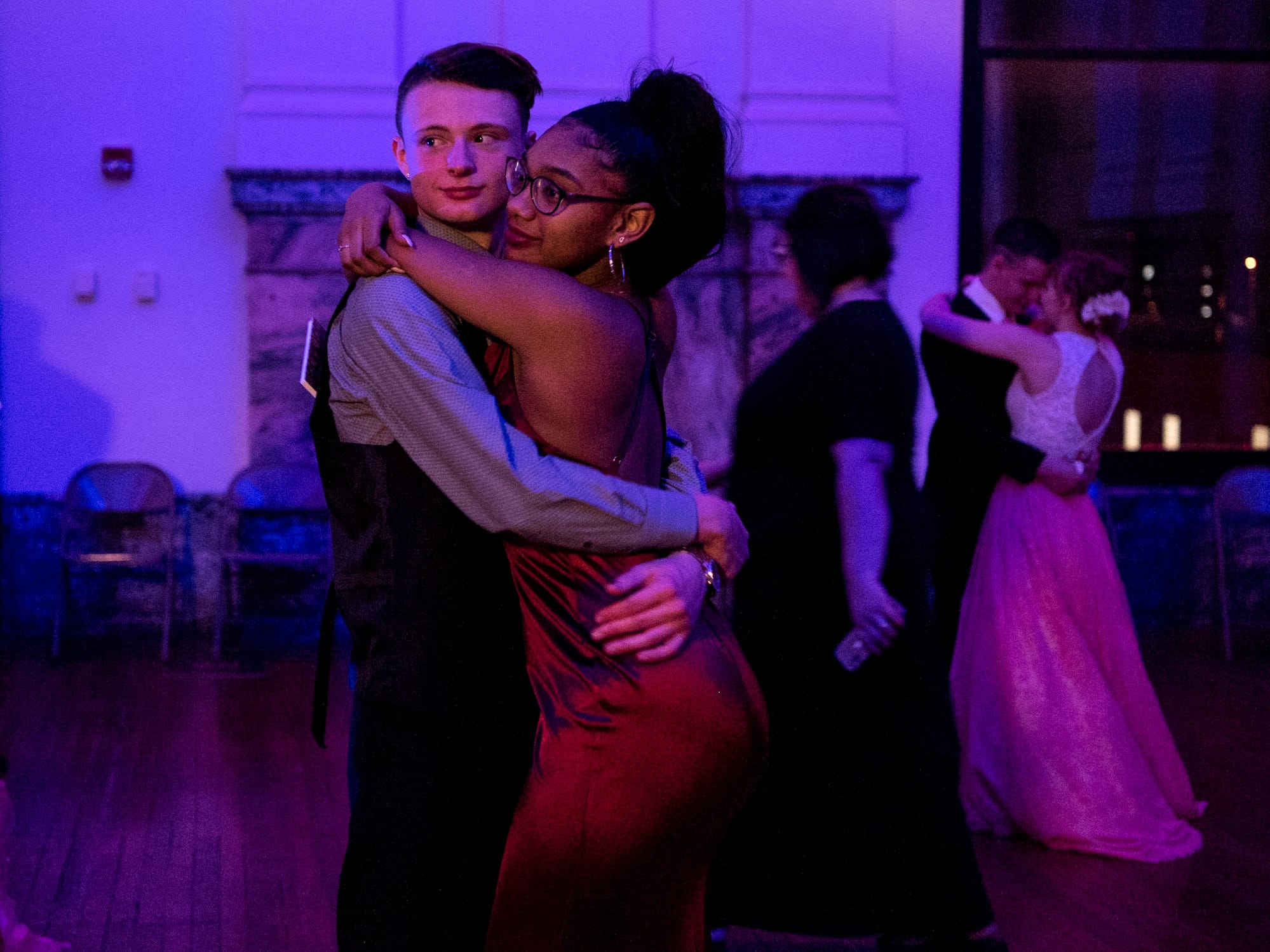 Peyton Lamar, front left, embraces his date Maleaya Labrador, front right, during a slow song at the dance held inside the Old Vanderburgh County Courthouse in downtown Evansville, Ind., Saturday, April 6, 2019.