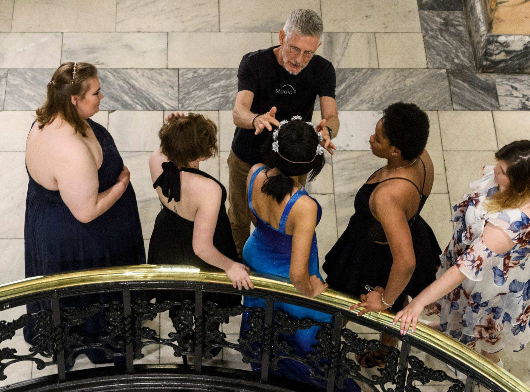 Daniel Knight, top center, of Studio B Photography poses Bosse High School students for a portrait during prom at the Old Vanderburgh County Courthouse in downtown Evansville, Ind., Saturday, April 6, 2019.