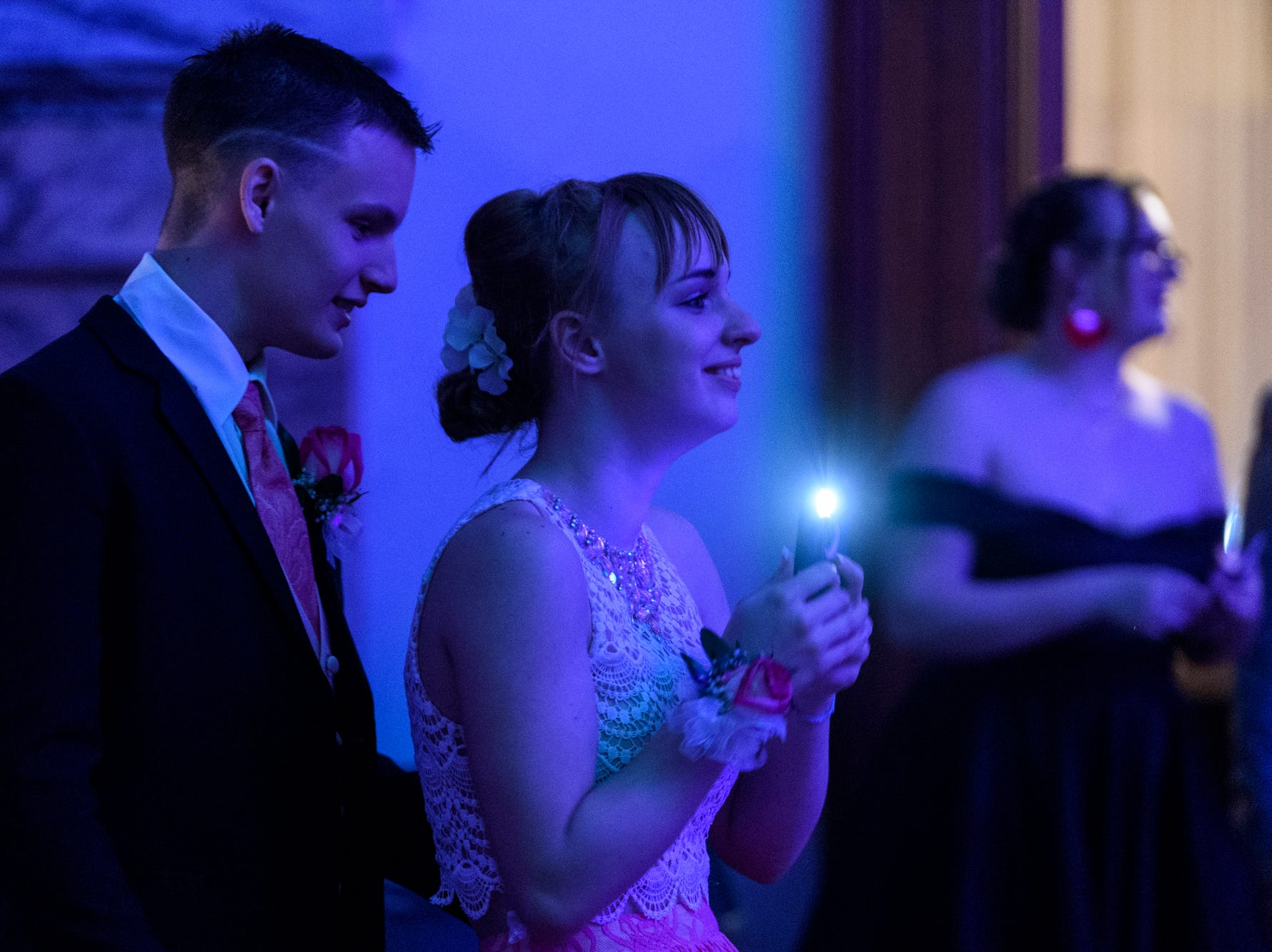 """Joseph Drury and Mary Devillez laugh as they watch people dance to the """"Cupid Shuffle"""" during Bosse High School's prom inside the Old Vanderburgh County Courthouse in downtown Evansville, Ind., Saturday, April 6, 2019."""