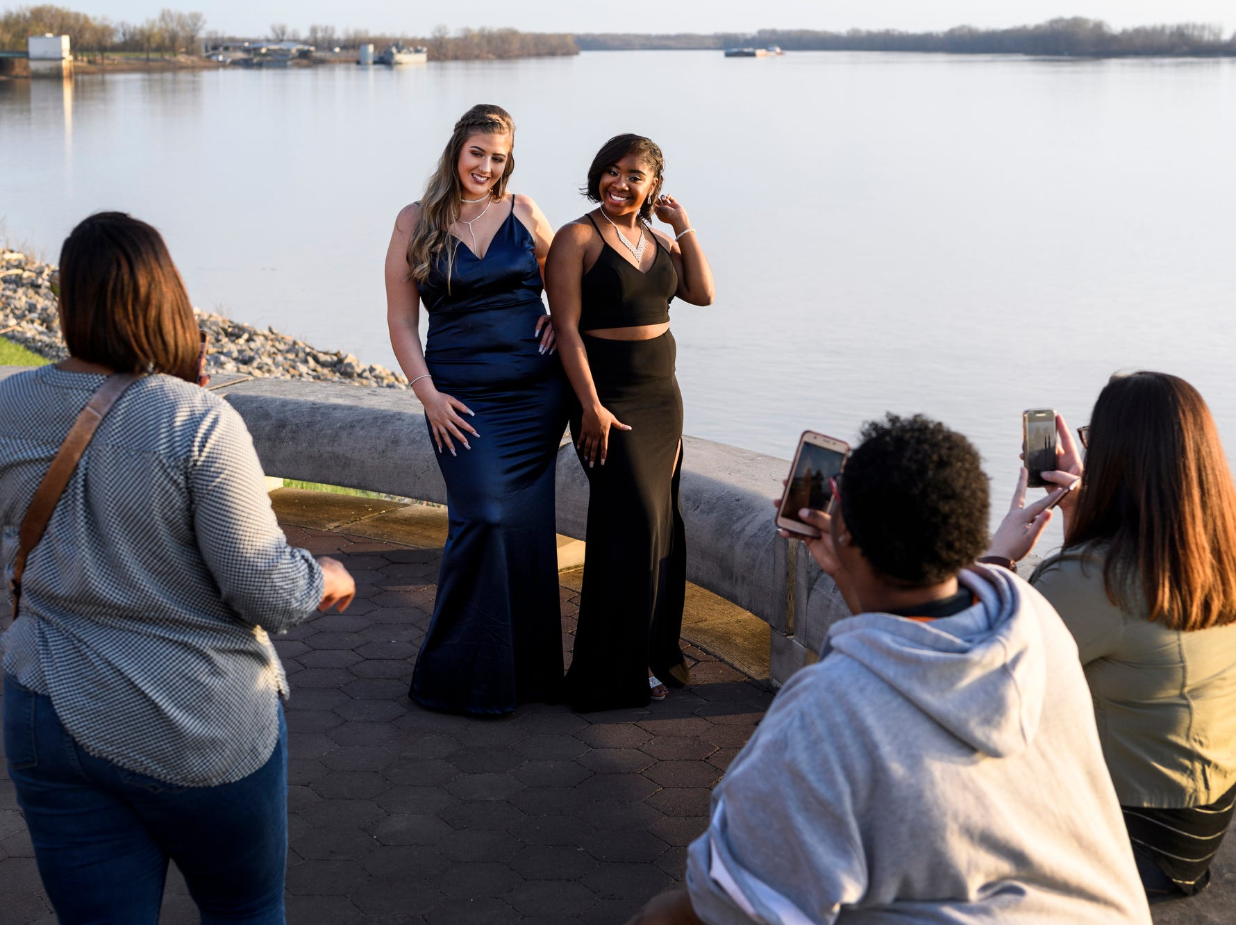Brittney Evans, center left, and Ayriana Meriwether, center right, use the Ohio River as their backdrop for pictures before going to Bosse High School's prom in downtown Evansville, Saturday, April 6, 2019.