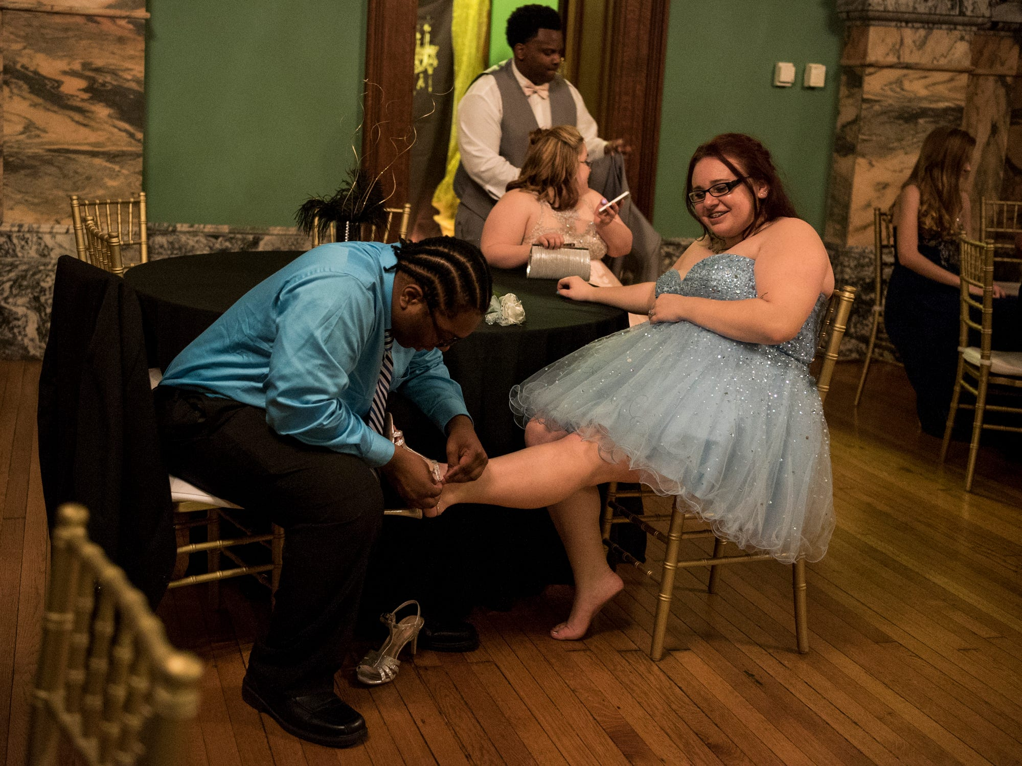 Sydney Mobley helps his prom date Majestica Weatherford put her shoes back on after a night full of dancing with their friends Cassidy Houston and Ethan Banks, both back, at the Old Vanderburgh County Courthouse in downtown Evansville, Ind., Saturday, April 6, 2019.