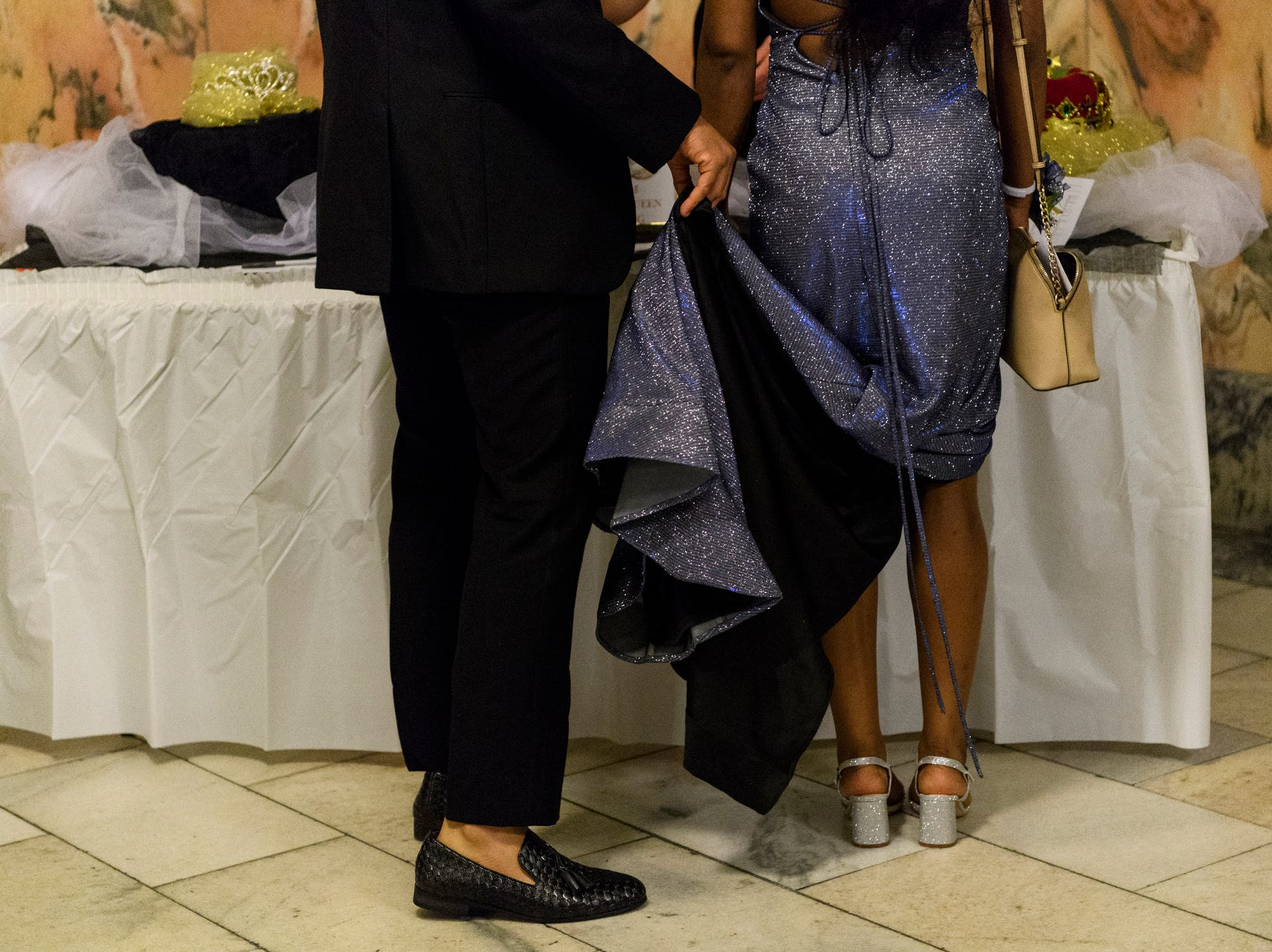 Darnell McRath Jr. holds his date Breasia Williams' dress as they prepare to vote for prom king and queen during dance at the Old Vanderburgh County Courthouse in downtown Evansville, Ind., Saturday, April 6, 2019.