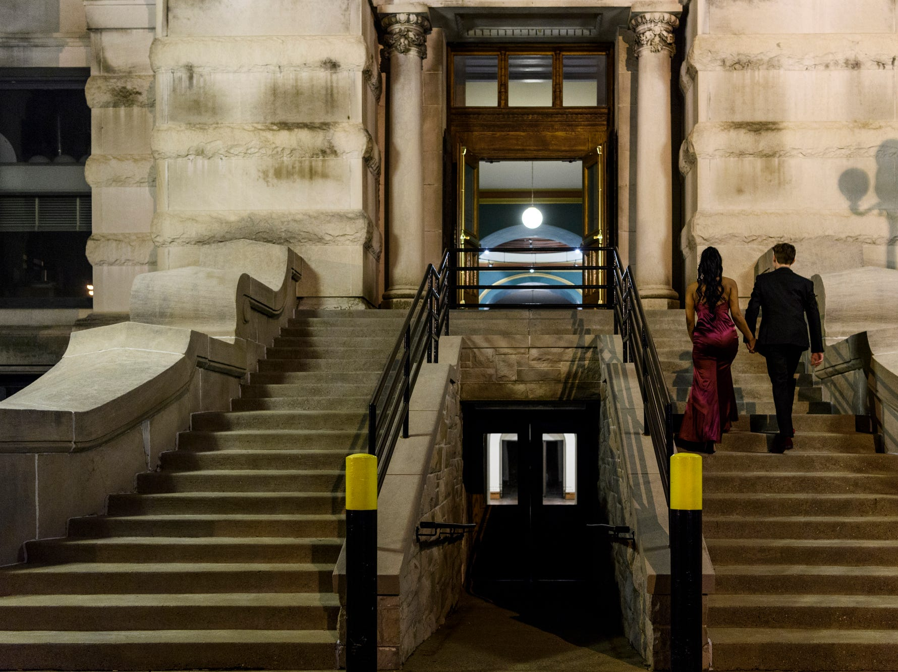 Maleaya Labrador and Peyton Lamar walk up the stairs of the Old Vanderburgh County Courthouse to attend Bosse High School's prom in downtown Evansville, Ind., Saturday, April 6, 2019.