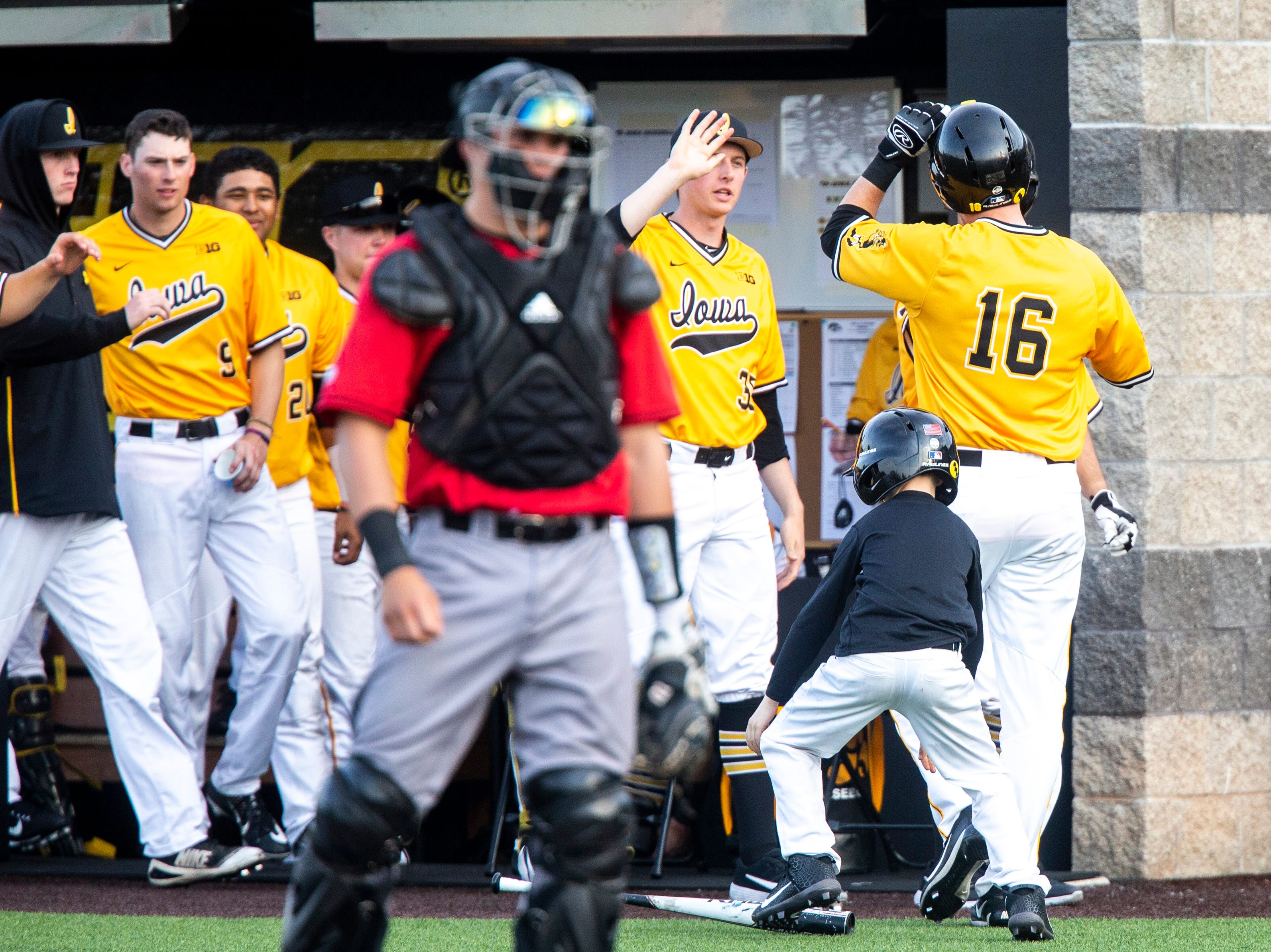 Iowa's Tanner Wetrich (16) gets a high-five after scoring a run during a NCAA Big Ten Conference baseball game on Saturday, April 6, 2019, at Duane Banks Field in Iowa City, Iowa.