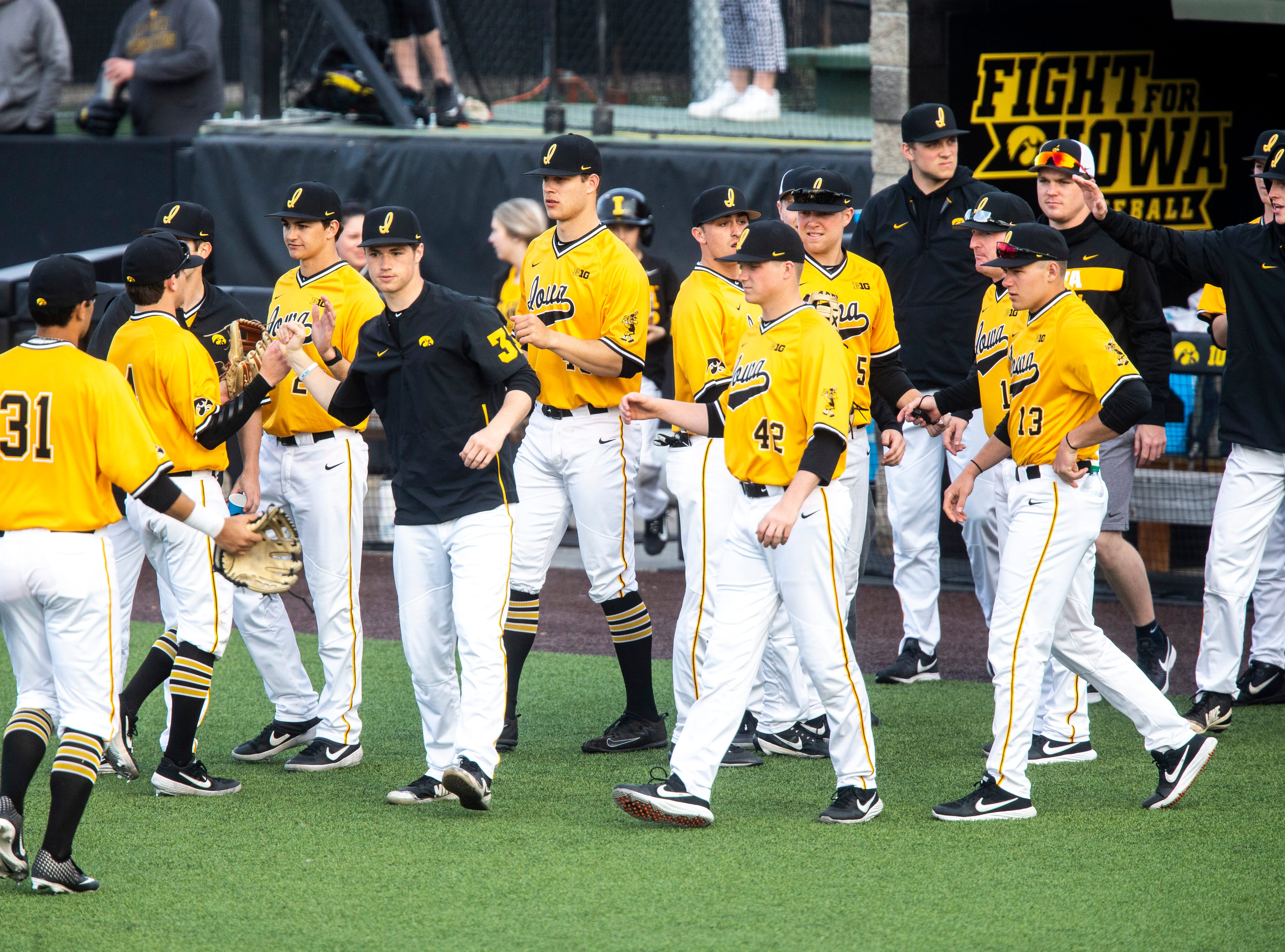 Iowa infielder Mitchell Boe gets a high-five from pitcher Jack Dreyer during a NCAA Big Ten Conference baseball game on Saturday, April 6, 2019, at Duane Banks Field in Iowa City, Iowa.