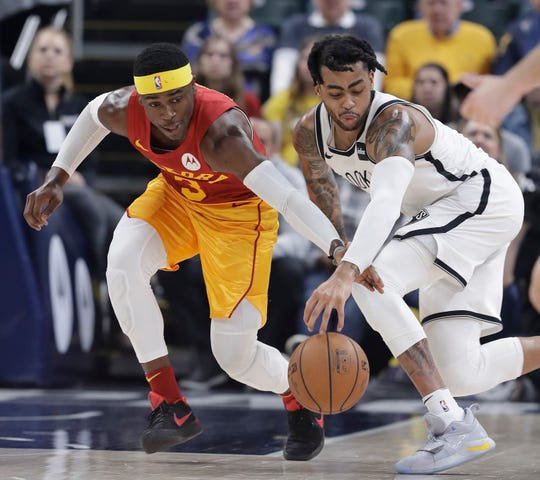 Indiana Pacers' Aaron Holiday (3) and Brooklyn Nets' D'Angelo Russell (1) go for a loose ball during the first half of an NBA basketball game Sunday, April 7, 2019, in Indianapolis.