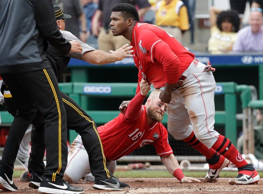 Cincinnati Reds' Yasiel Puig, right, gets away from Tucker Barnhart (16) as he attempts to re-enter a bench clearing during the fourth inning of a baseball game against the Pittsburgh Pirates in Pittsburgh, Sunday, April 7, 2019.