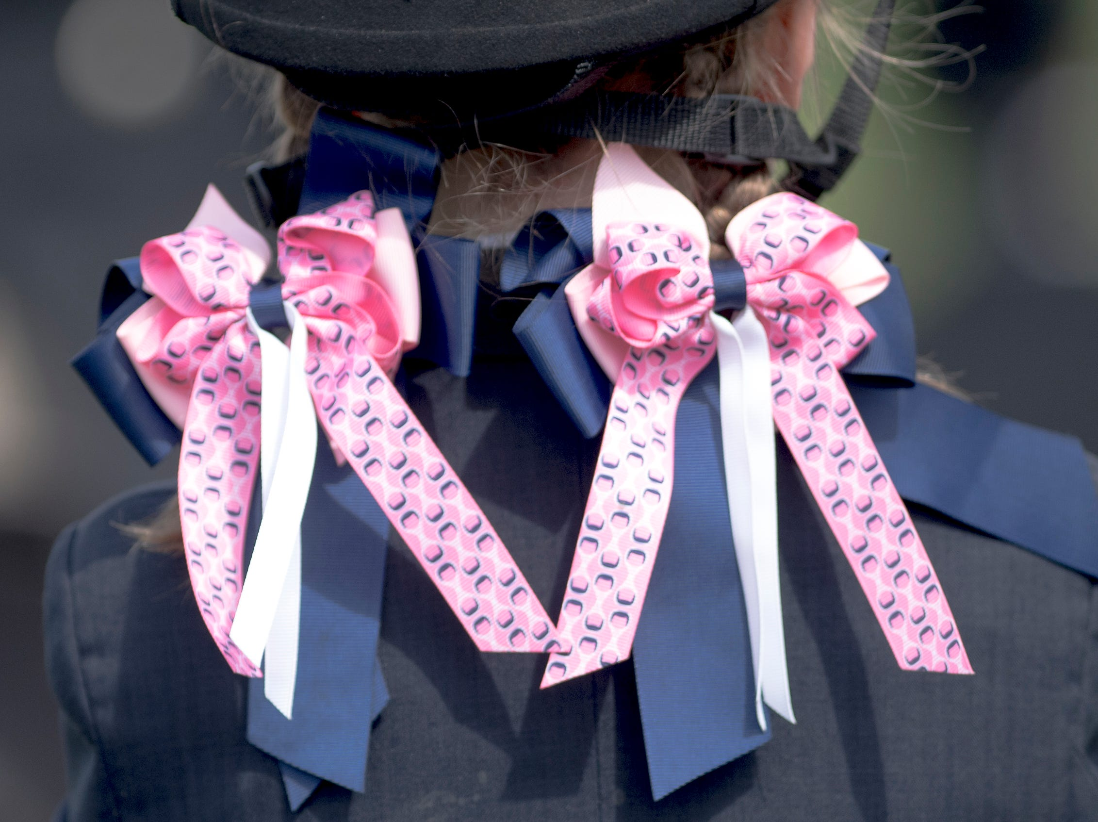 Tinsley Saunders, 7, of Knoxville, wears ribbons in her hair while riding her pony, Riot, during a fixture at Blackberry Ridge Farm in Greeneville, Tennessee on Saturday, March 30, 2019. Younger girls wear ribbons in their hair as a gesture of respect to the master huntsman.