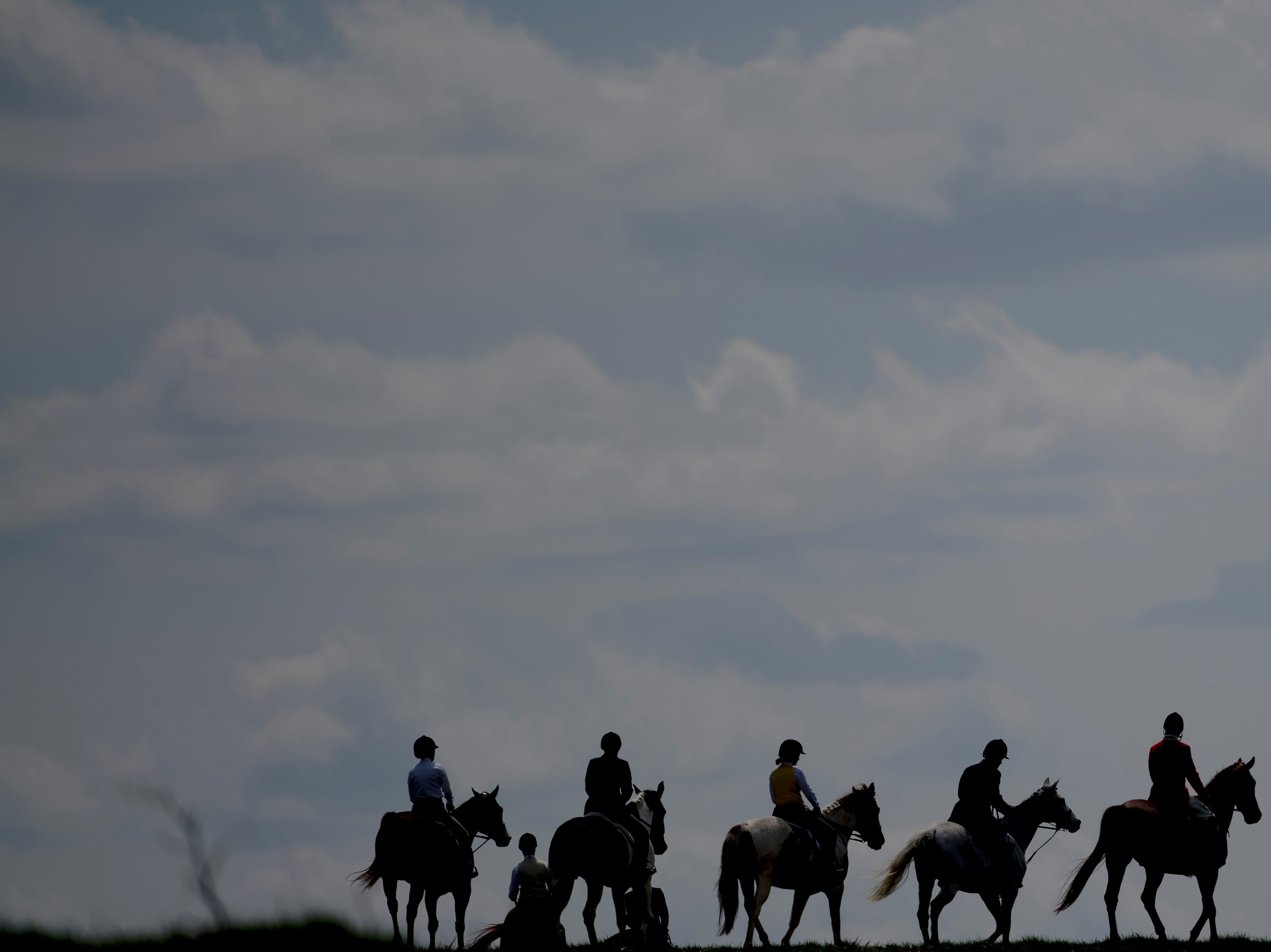 A row of hunters walk along the top of a hill during a fixture at Blackberry Ridge Farm in Greeneville, Tennessee on Saturday, March 30, 2019.