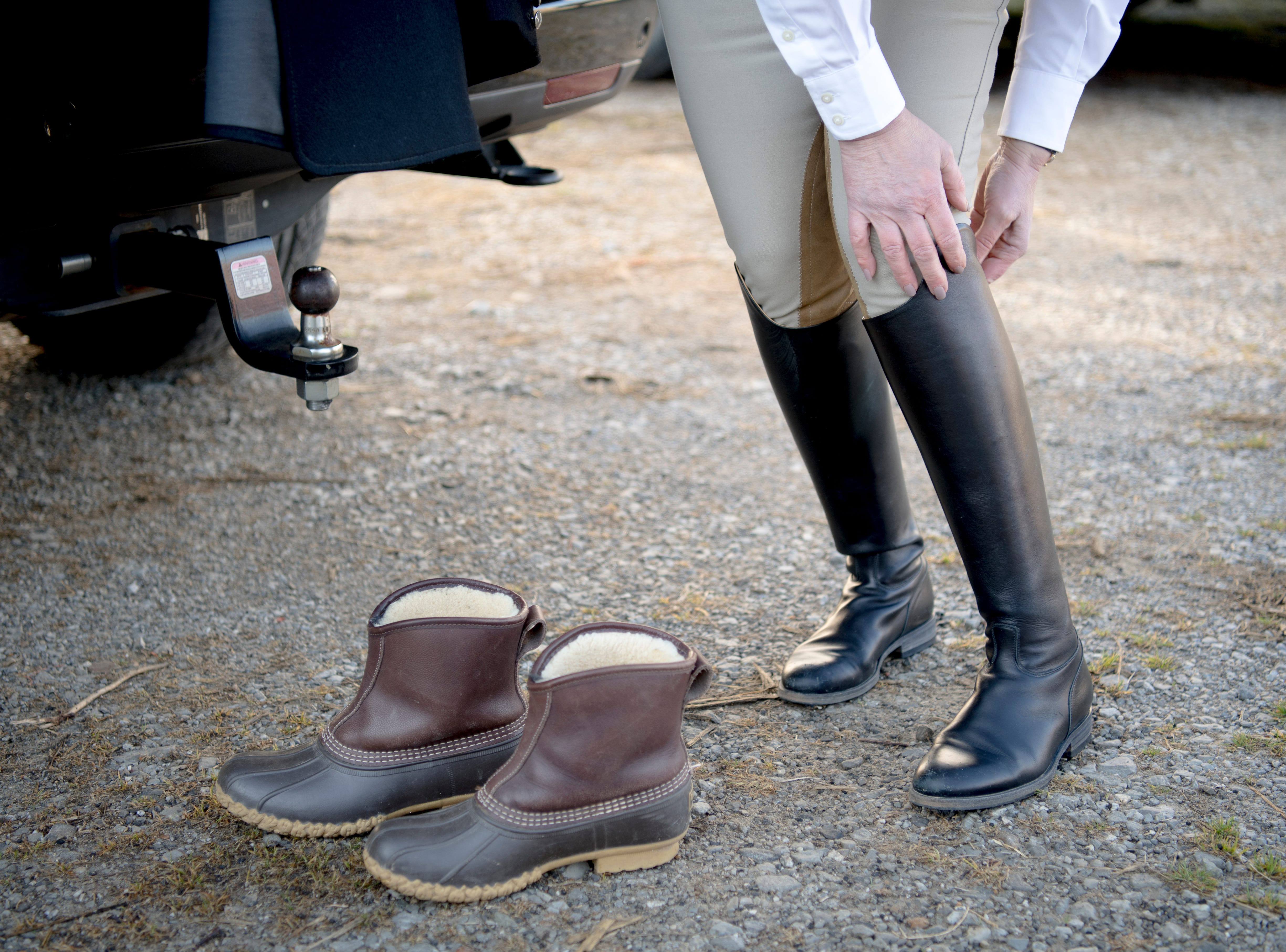 A rider puts on tall leather riding boots, which offer leg protection for horseback riders, before a fixture at Riverplains Farm in Strawberry Plains, Tennessee on Wednesday, March 27, 2019.