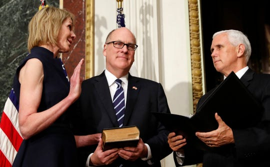 Vice President Mike Pence swears in the U.S. Ambassador to Canada Kelly Knight Craft, as her husband Joe Craft holds a bible, in the Indian Treaty Room in the Eisenhower Executive Office Building on the White House grounds, Tuesday, Sept. 26, 2017, in Washington. (AP Photo/Alex Brandon)